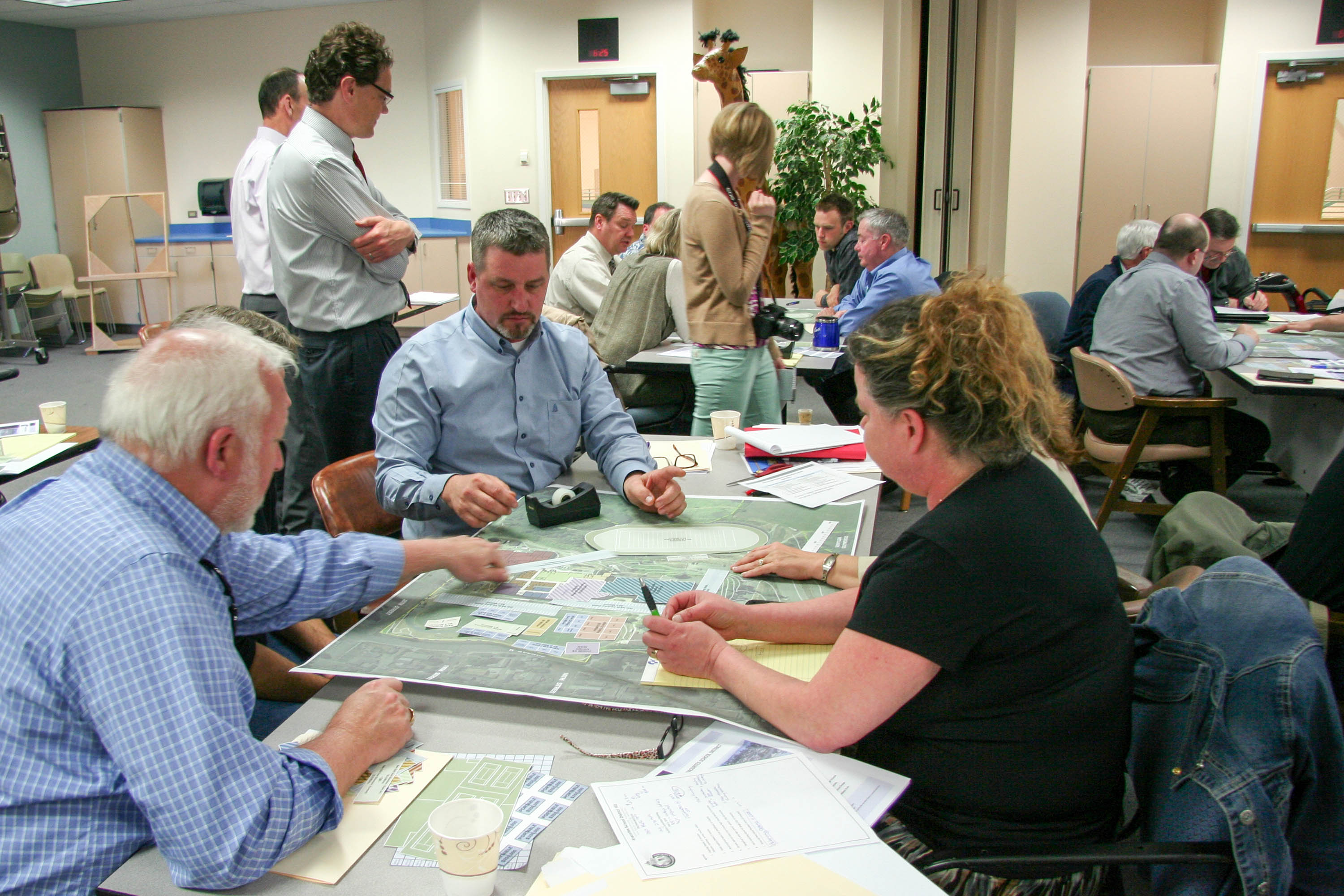 Staff, district, and community members sitting at a table in discussion.