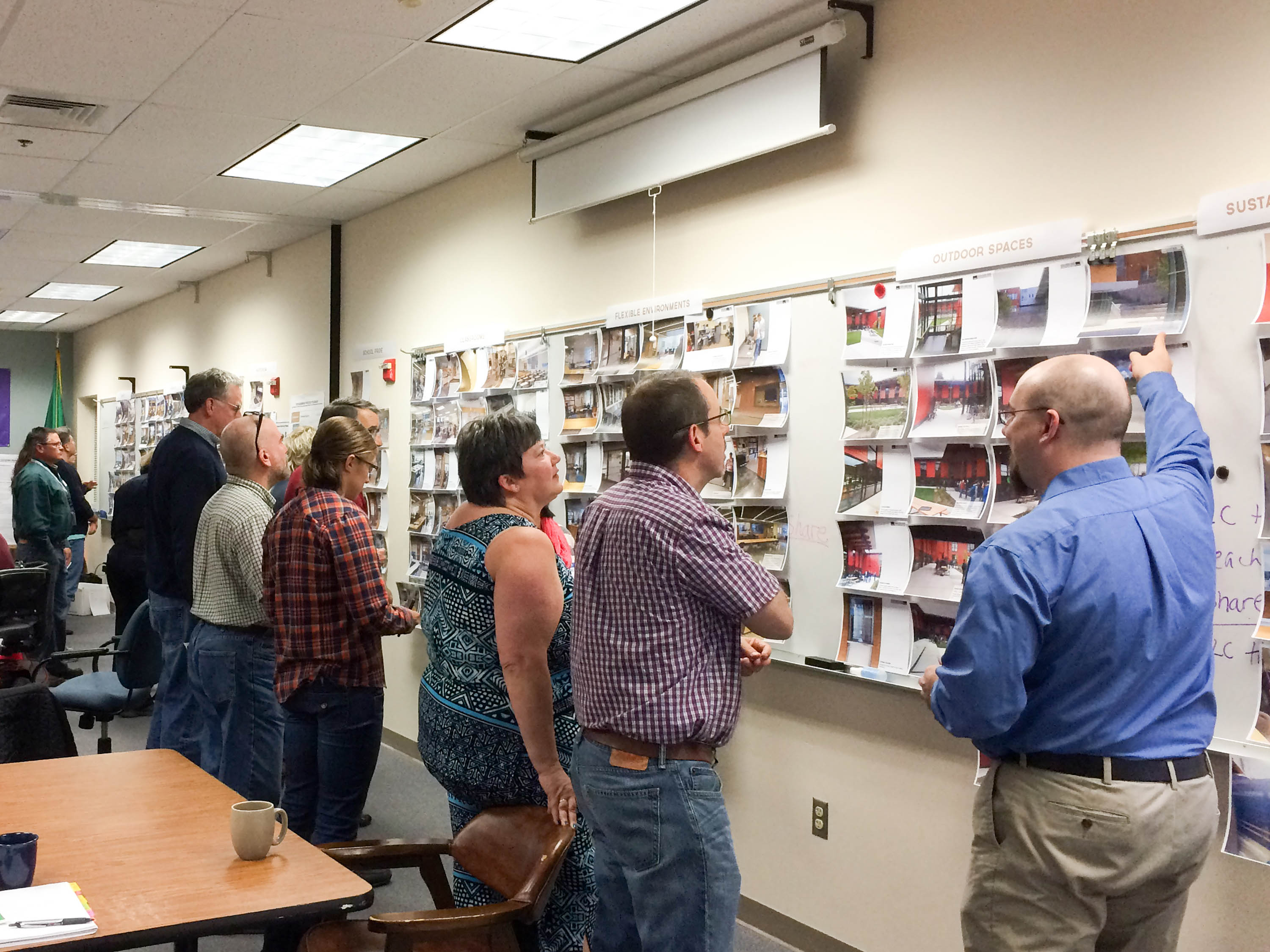 Multiple people standing up and looking over renderings.