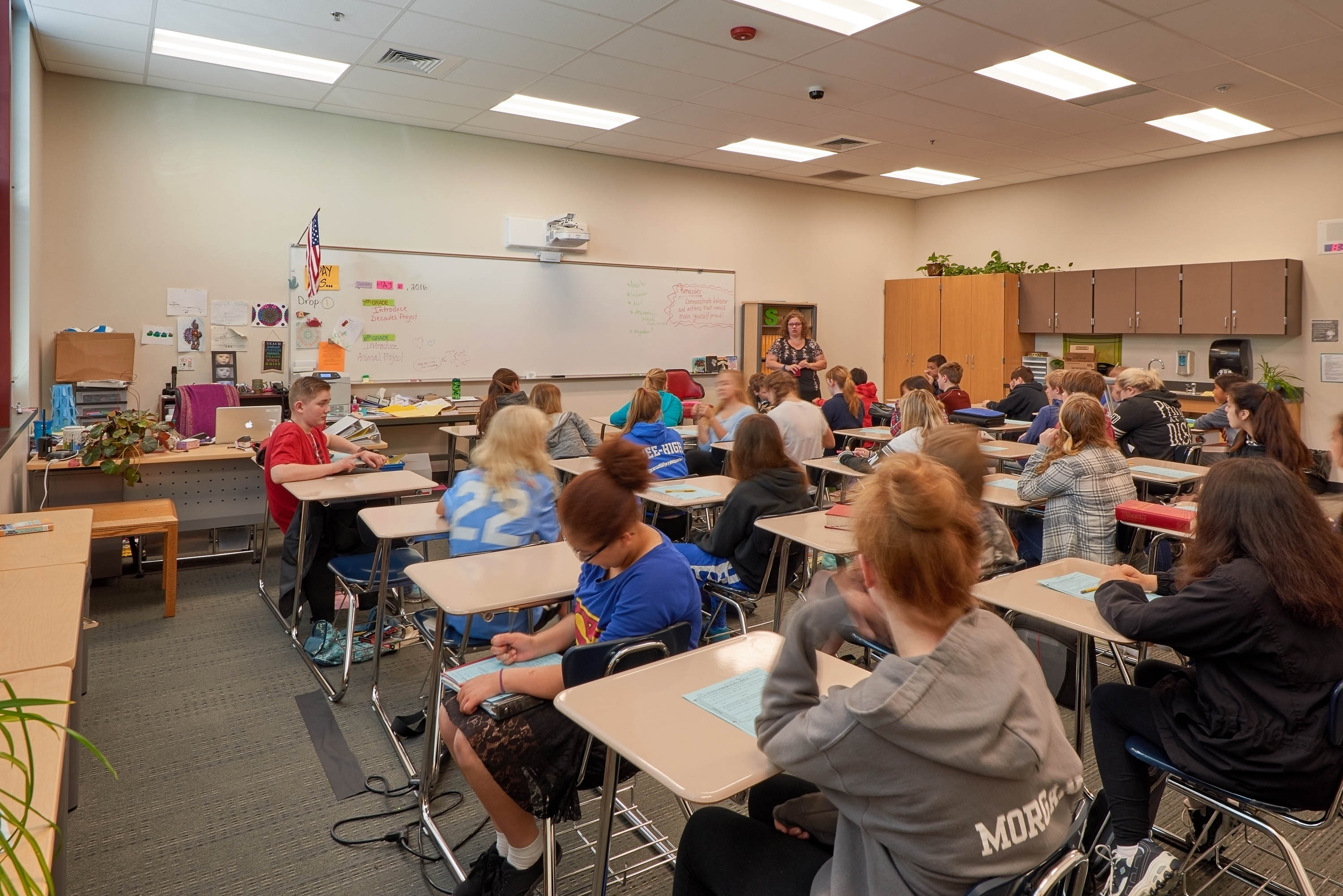 Students in a classroom at their desks listening to a teacher.