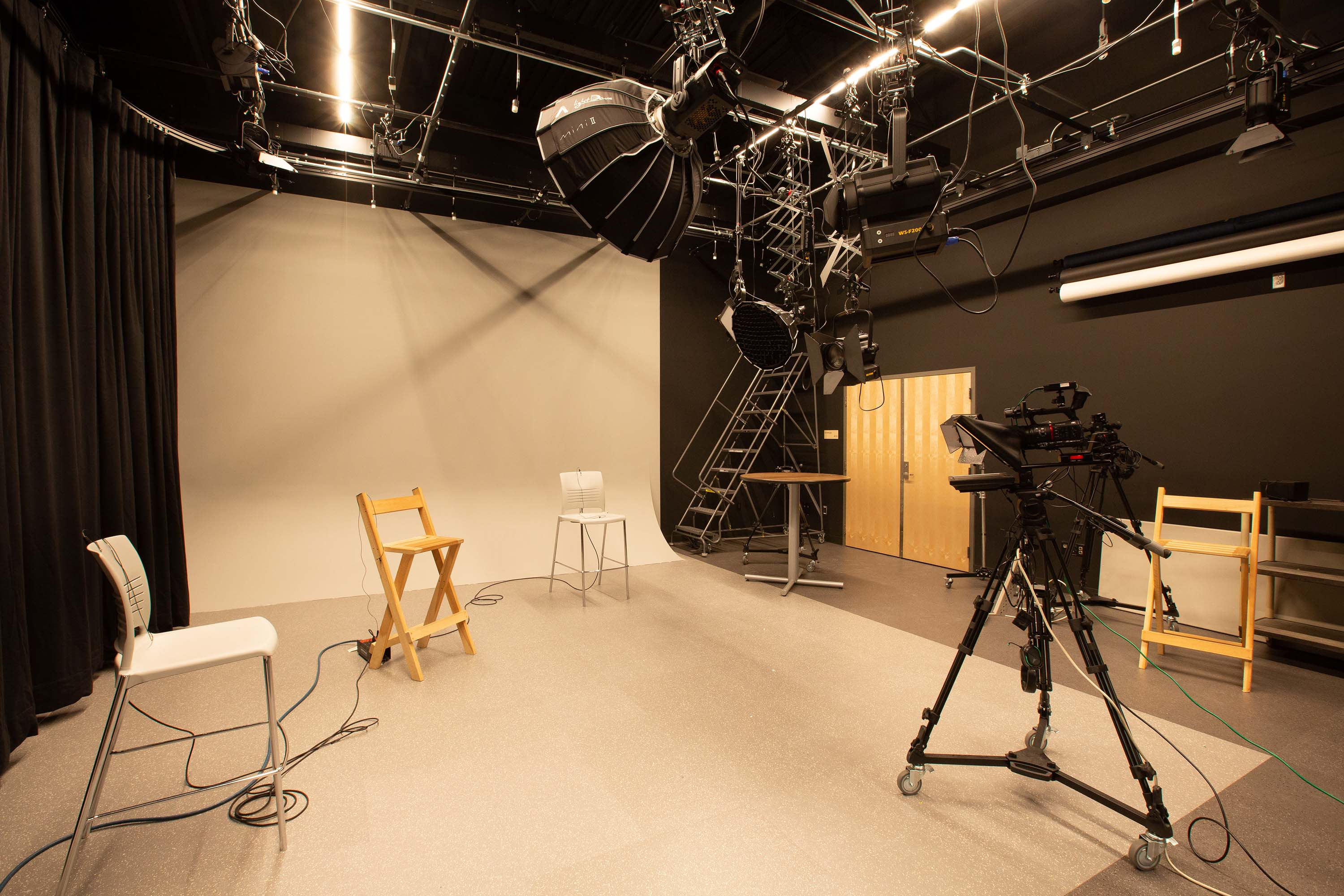 Studio setup for recording film with lights and a backdrop.