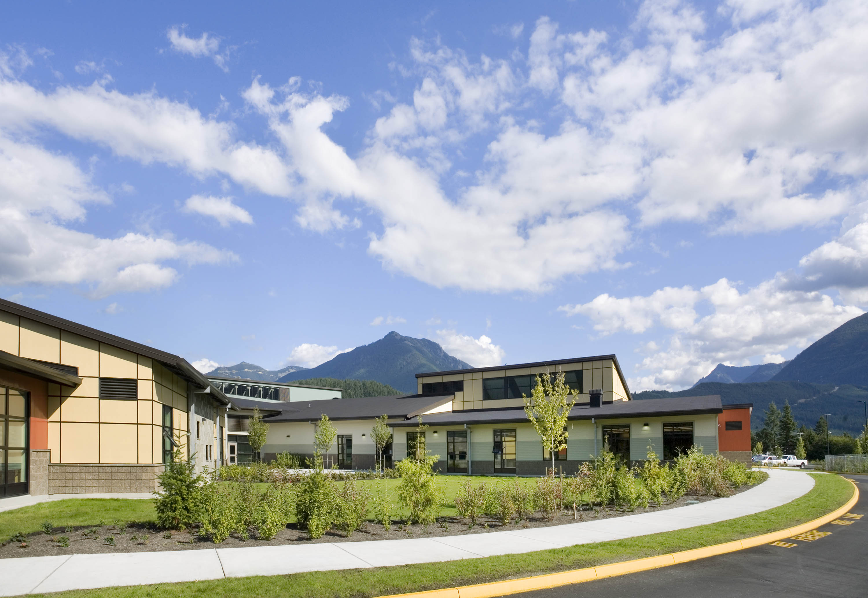 Angled photo of the school with mountains in the background.