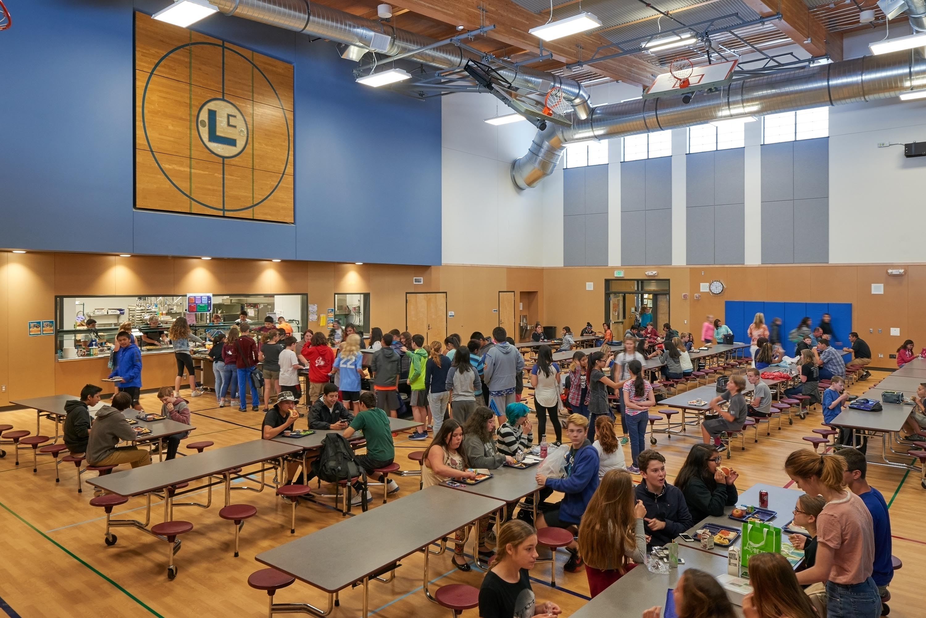 Wide photo of the lunchroom and students eating.