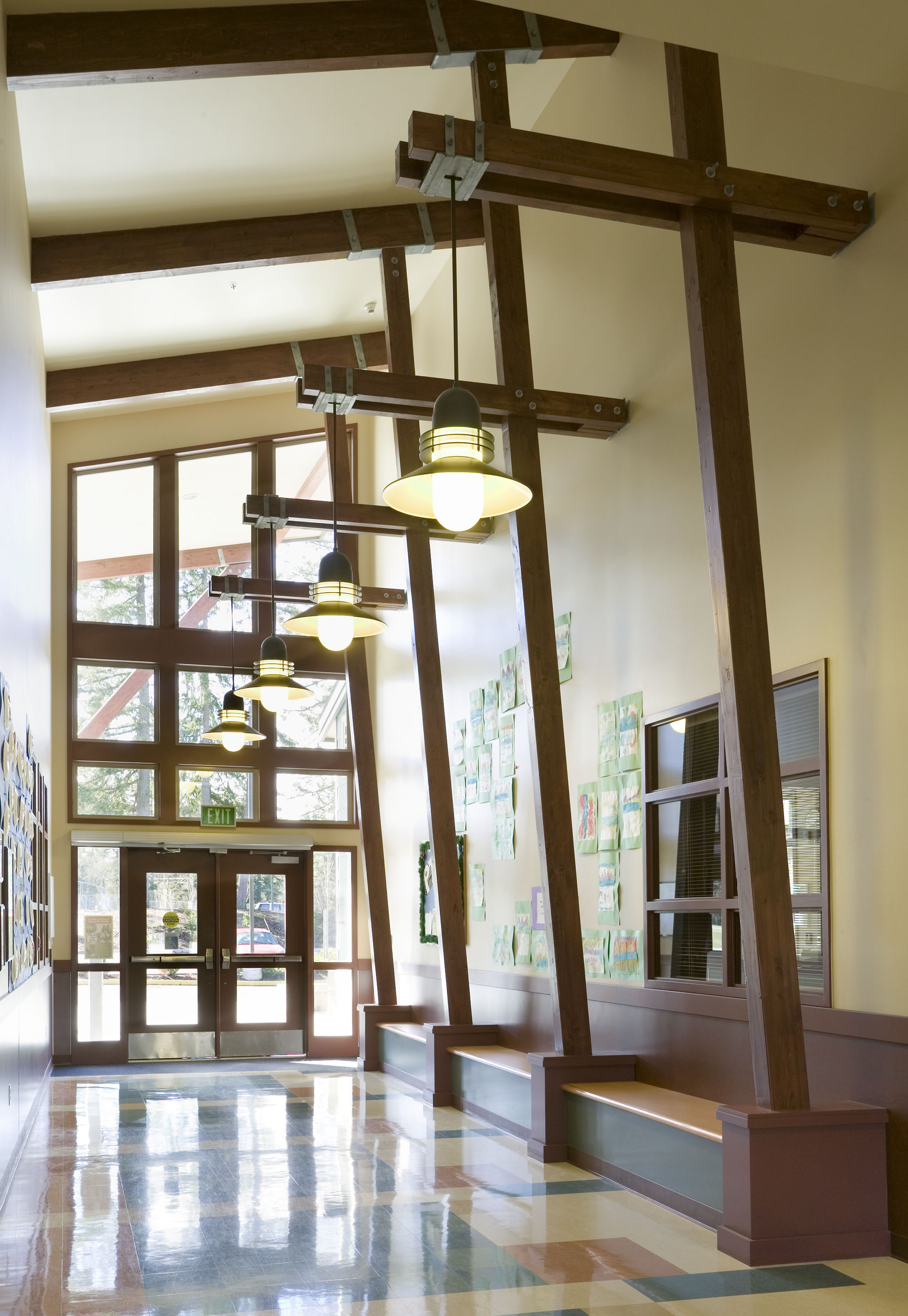 Hallway leading to outside with tall wood beams.