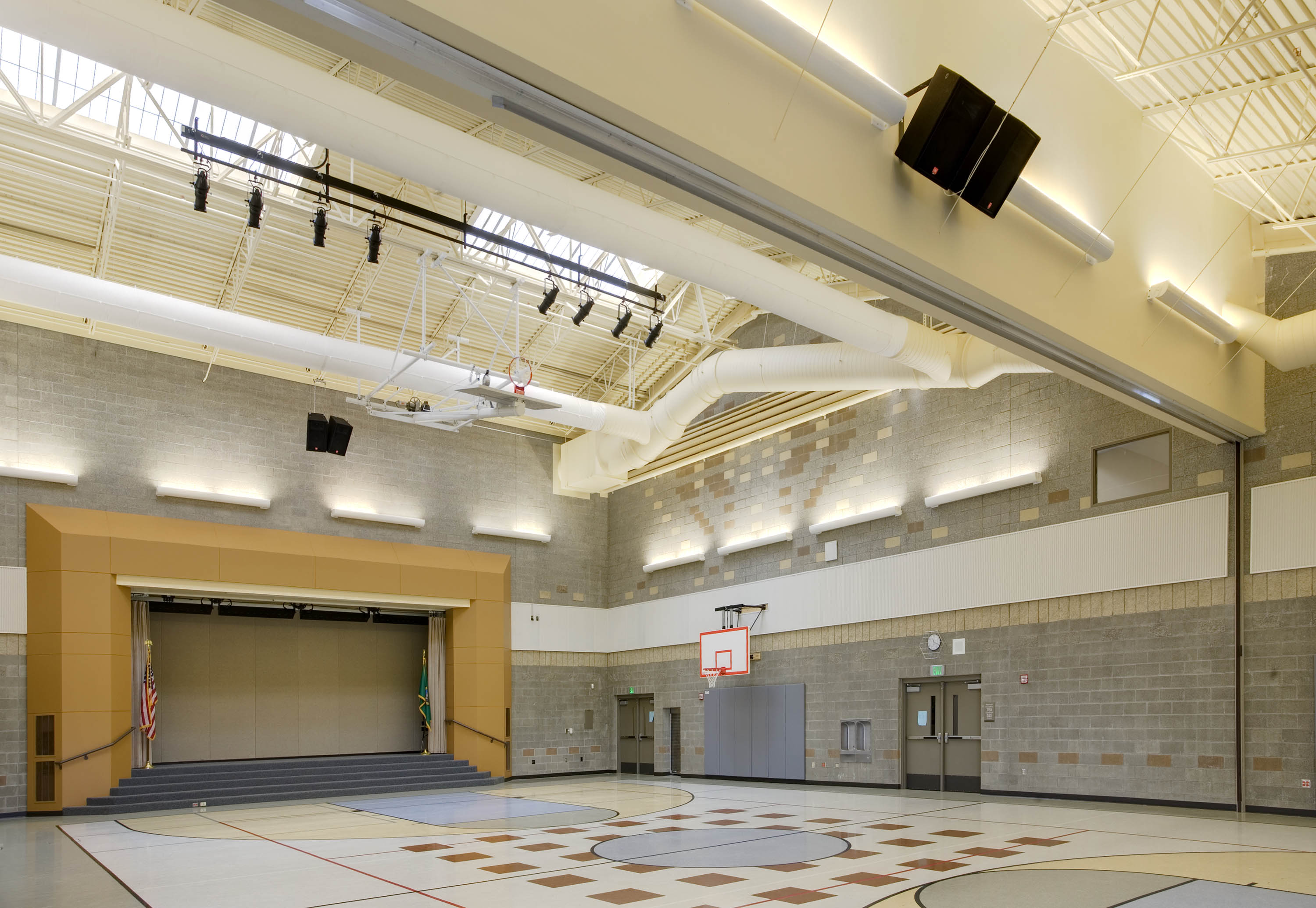 Multi use room with a stage and a basketball court.
