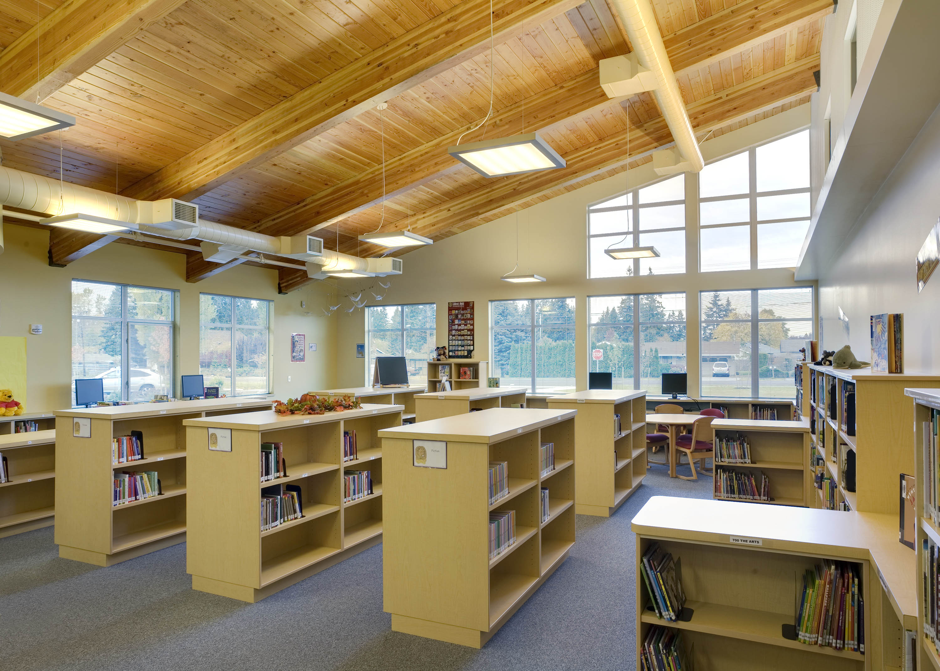 Wide photo of the library with wood ceilings and window light coming in.
