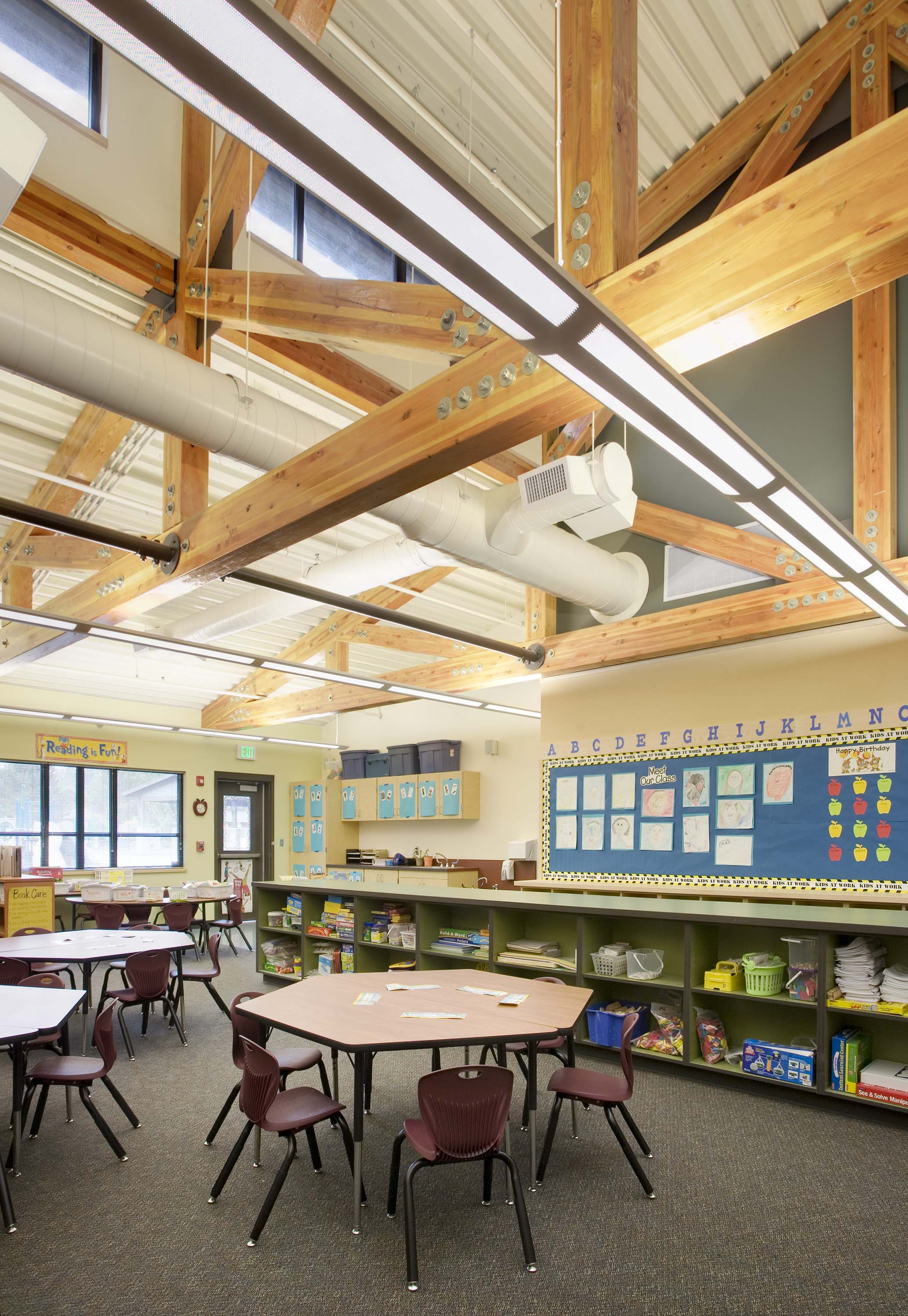 Art classroom with high ceilings and wood beams.