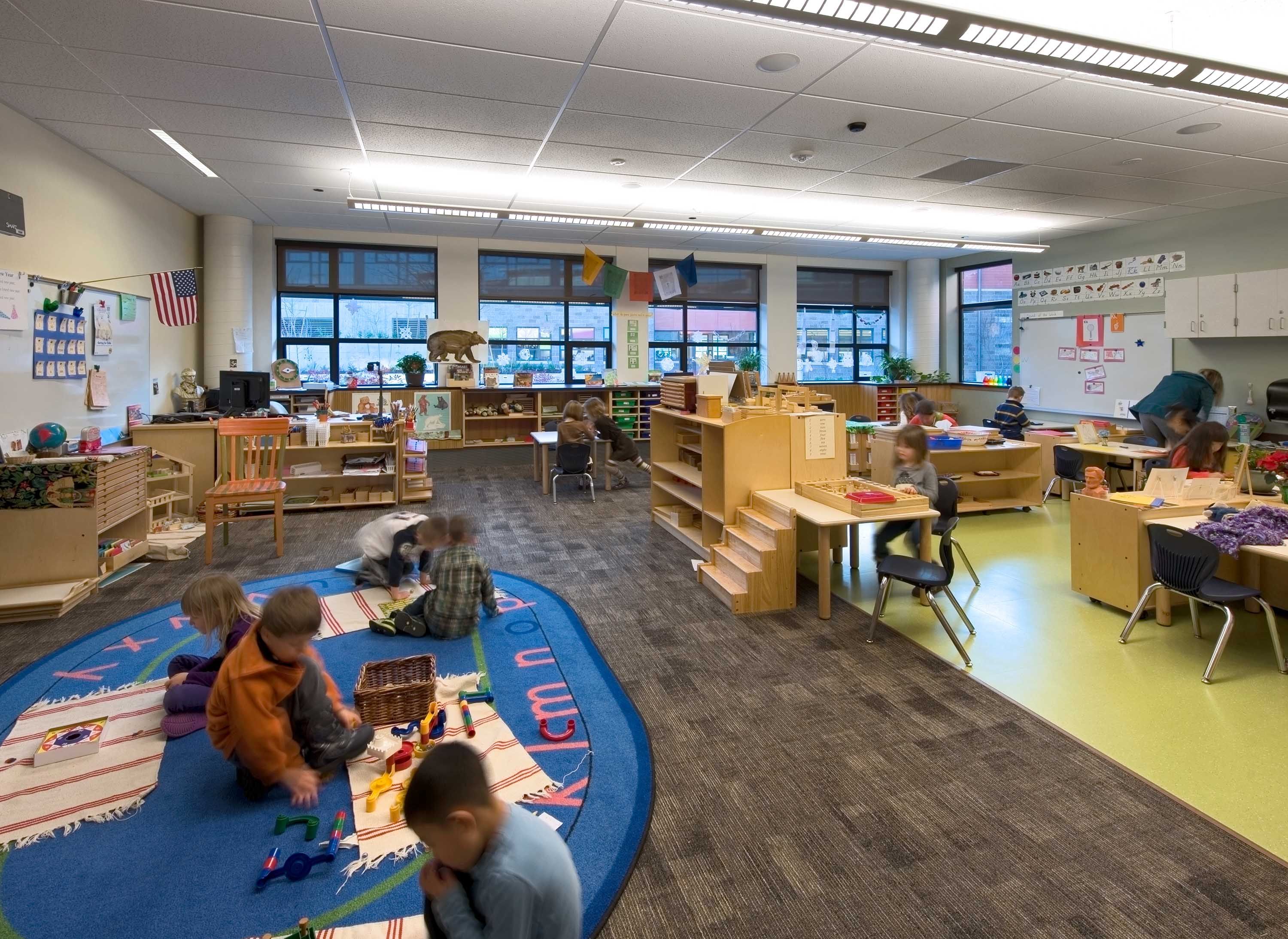 A wide photo of the library with students learning at multiple areas of the room.