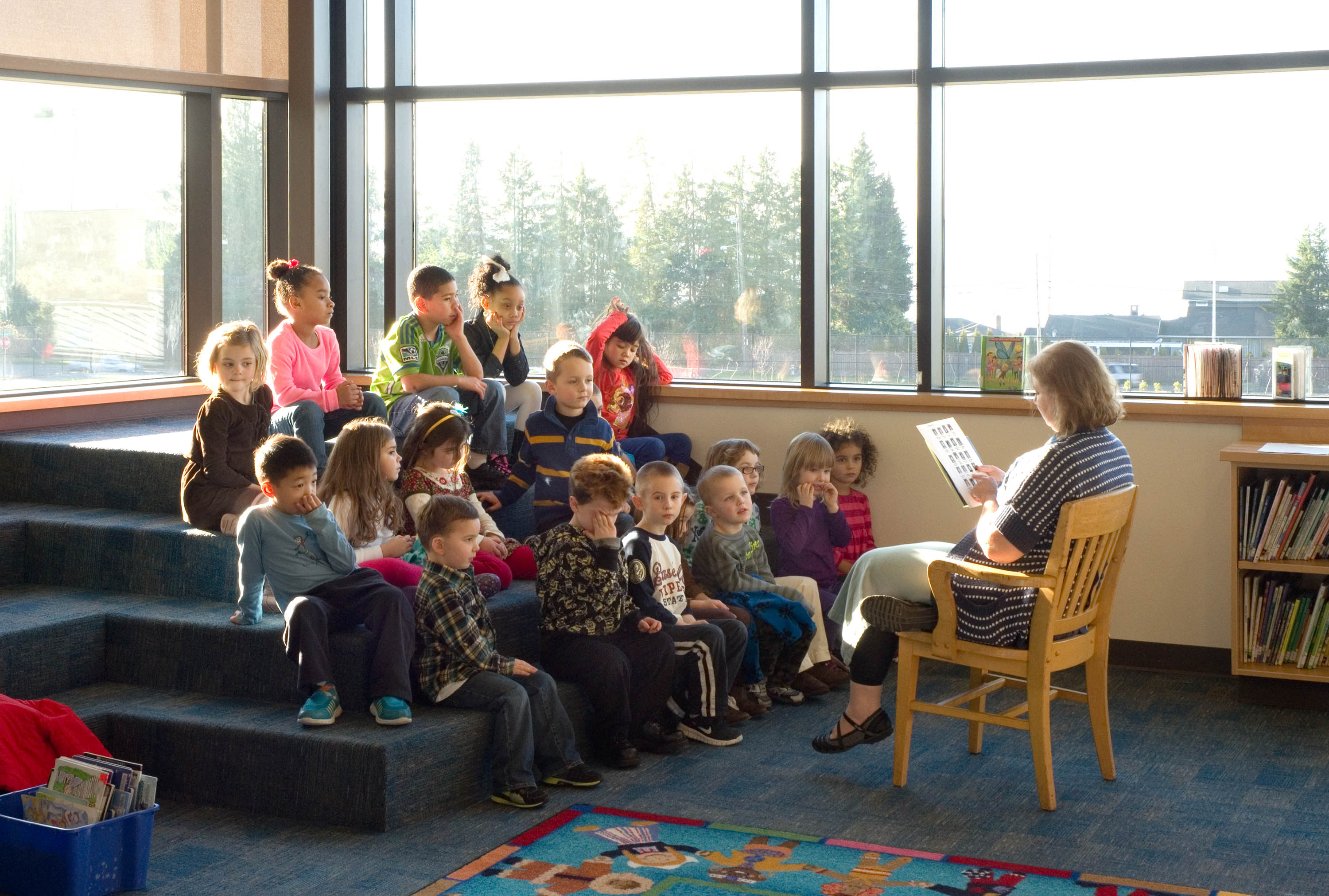 A teacher reading to a group of students in the library.