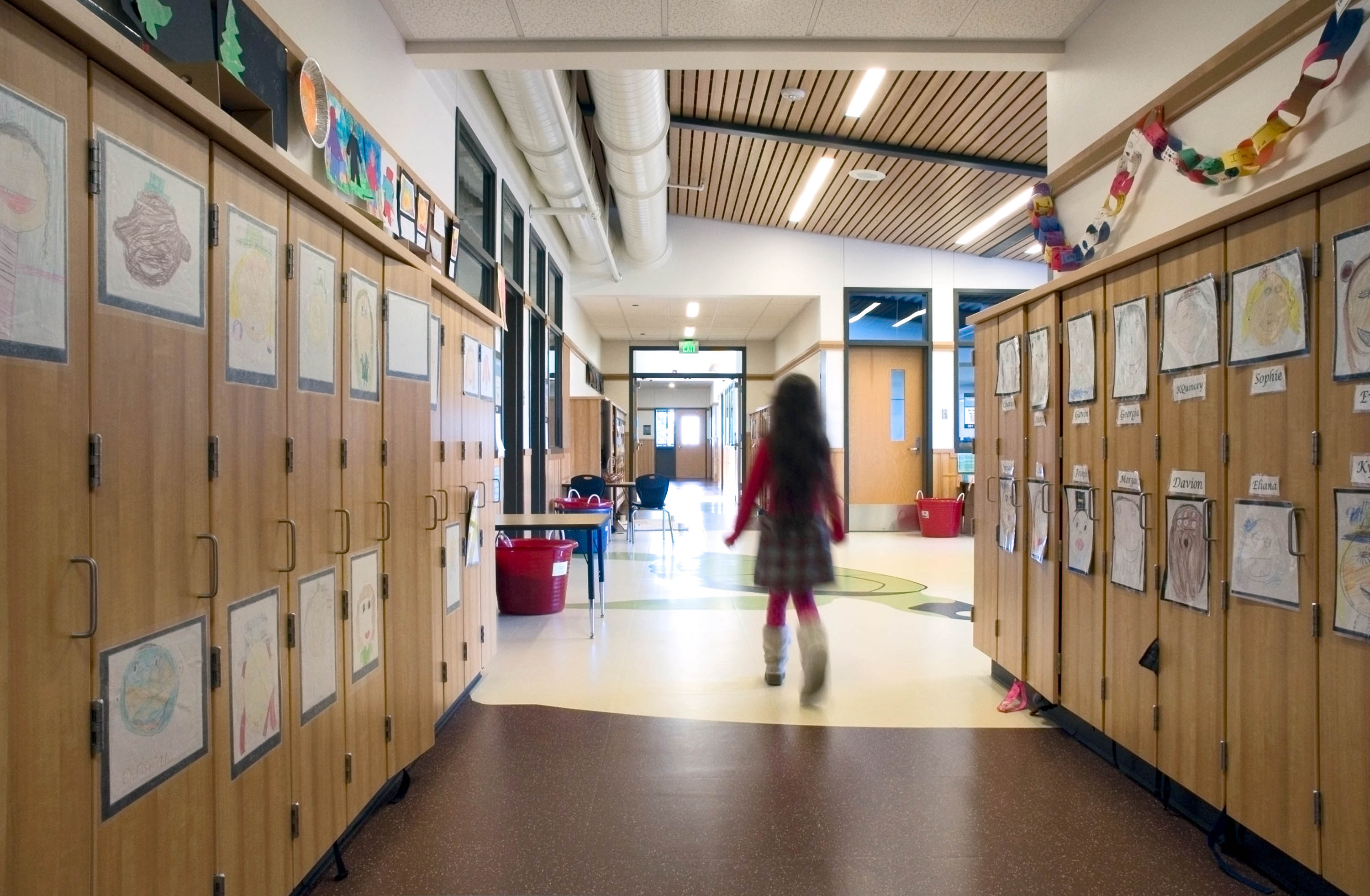 A student walking past lockers in a hallway.