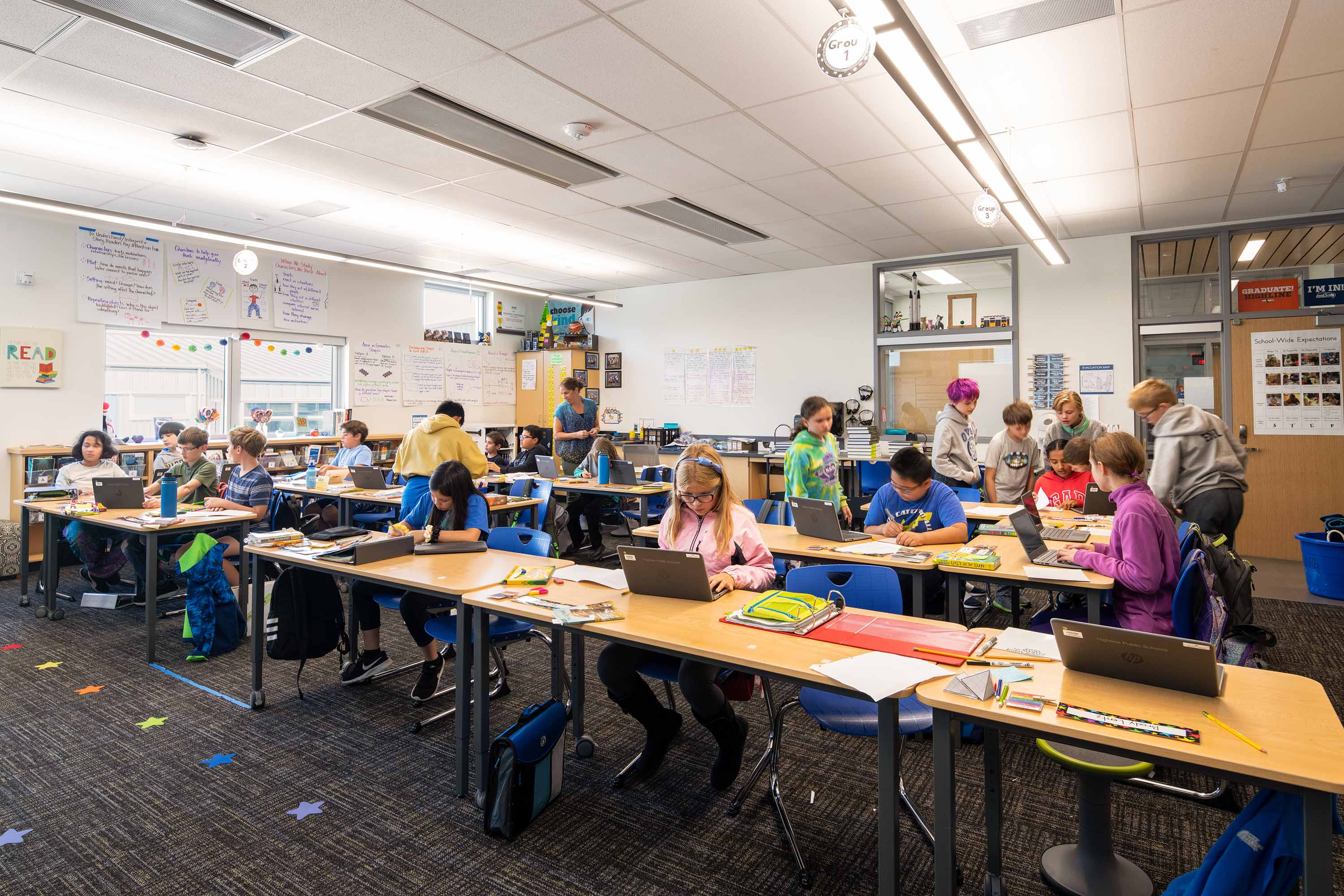 Students working in a classroom on laptops.