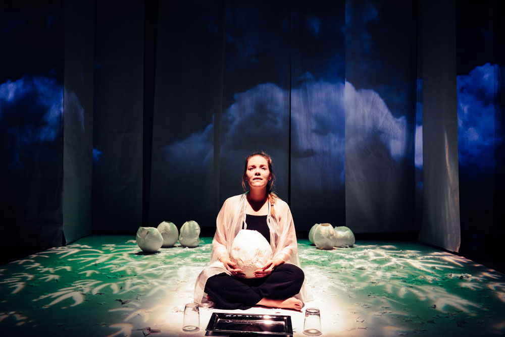 woman sitting center stage in a forest