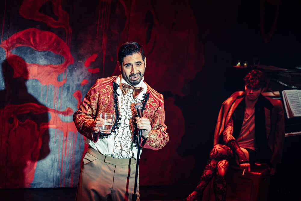 Man singing into microphone dressed in snazzy red suit