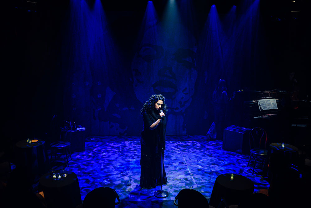 woman performs solo on stage in deep blue lighting