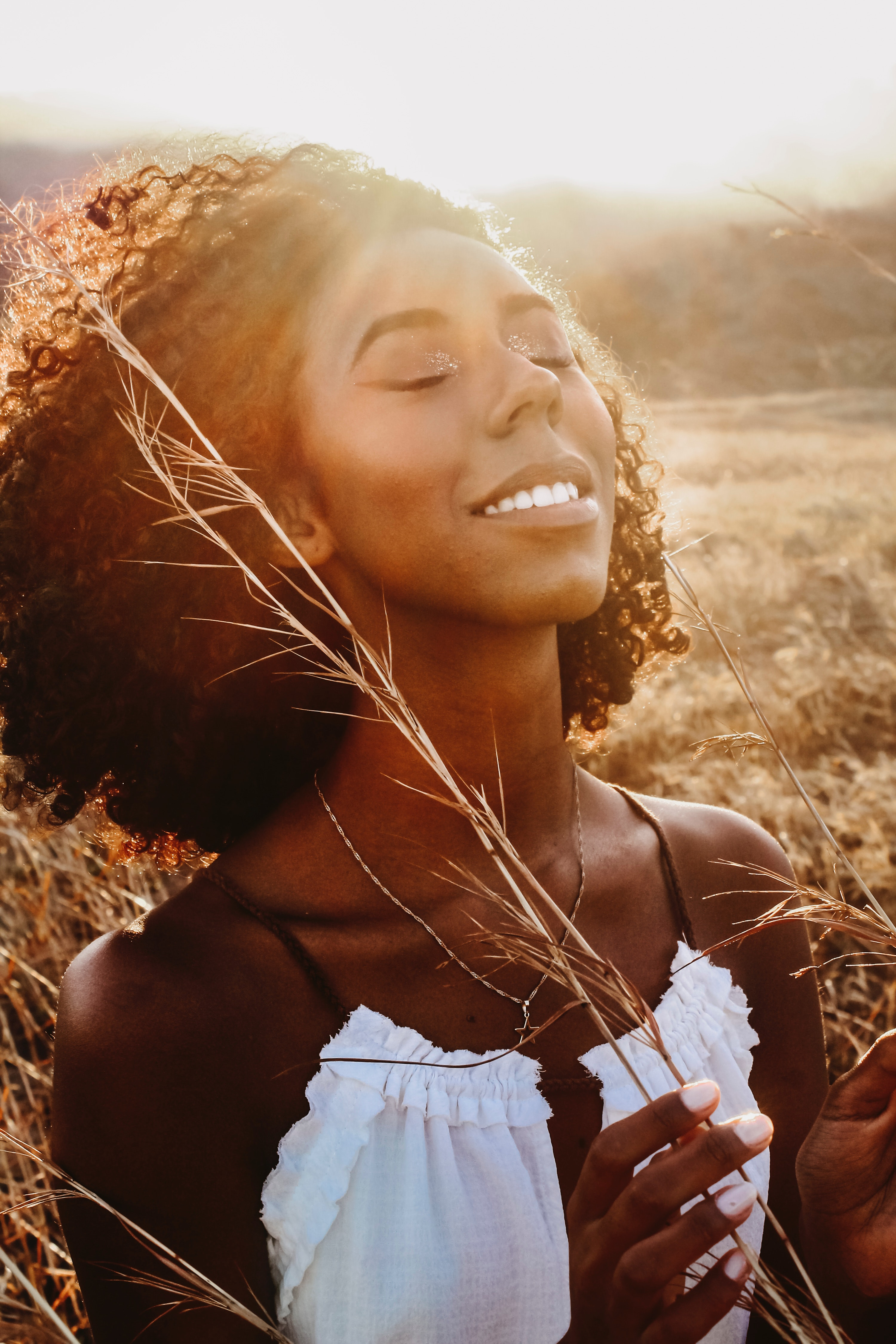 A Black woman serenely standing in a field with her eye closed
