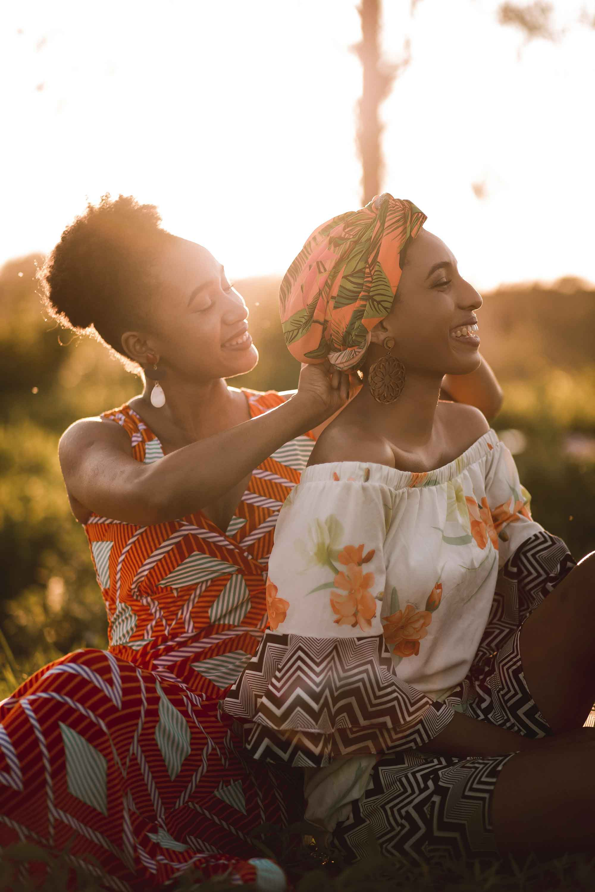 Two Black Woman happily sitting outside in the grass. One is adjusting the other's head-tie