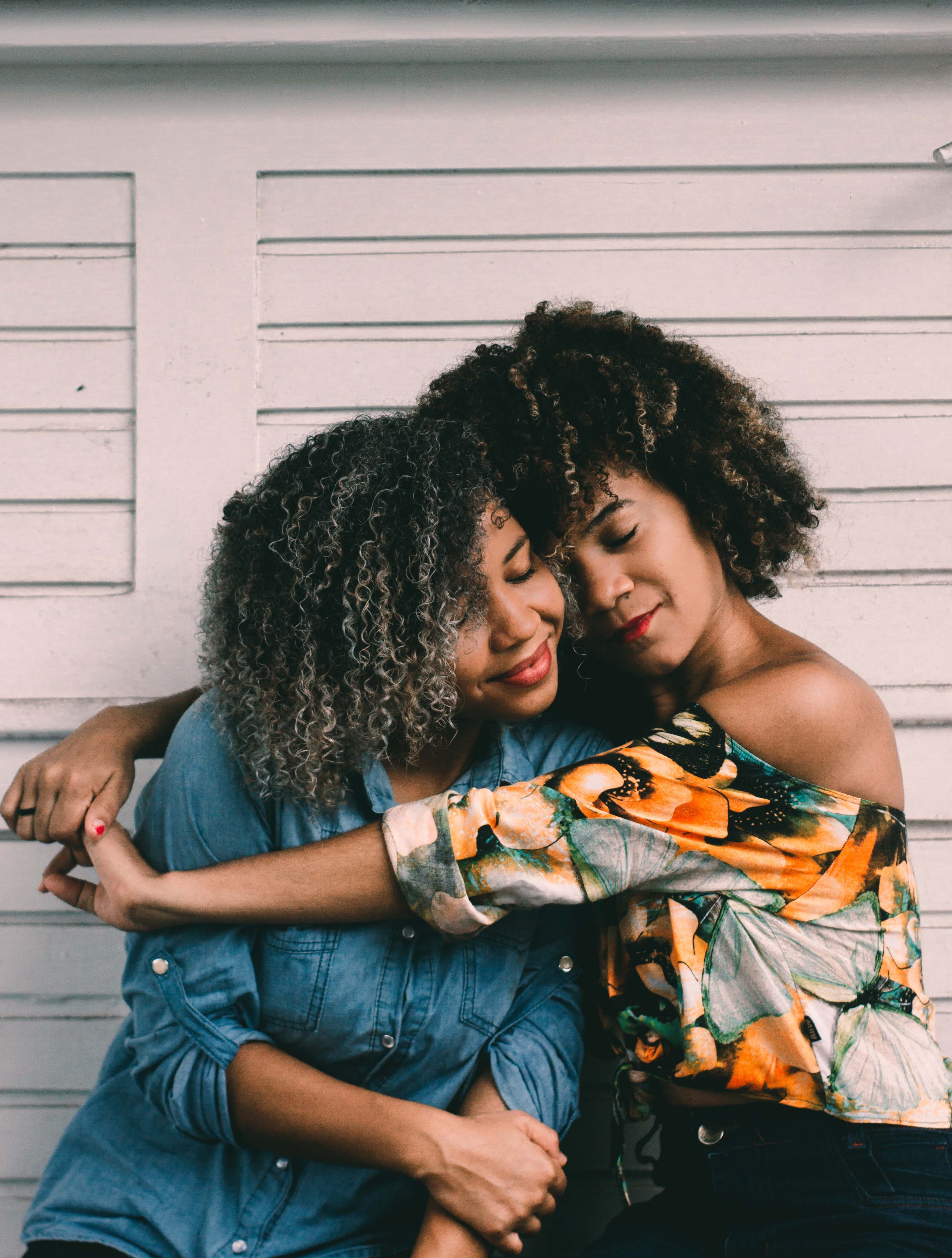 Two Black women embracing peacefully