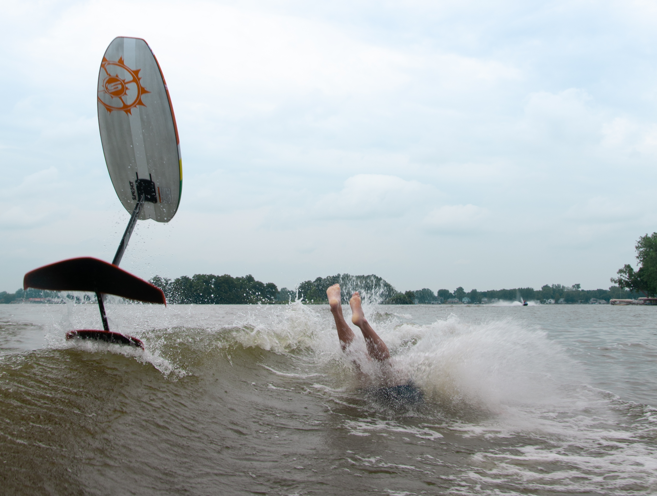 A surfboard with a foil popping into the air while the rider is upended into the water