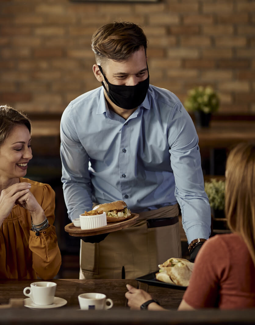 Server delivering food to table with a face mask on