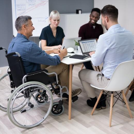 man in wheelchair in office meeting