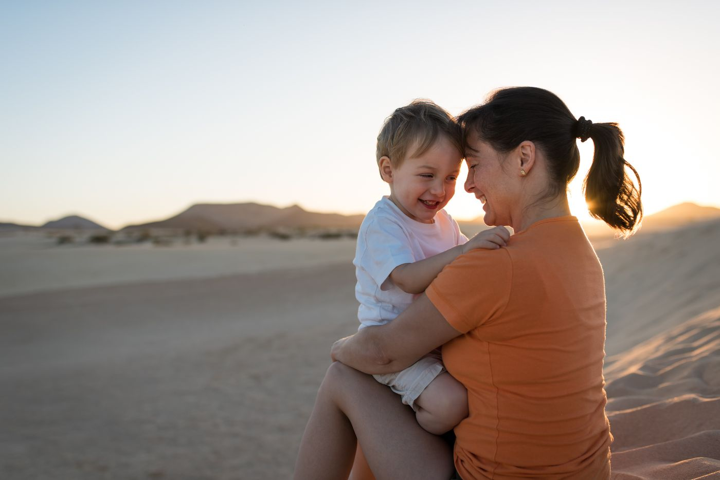 Mom and son playing in desert sand around sunset