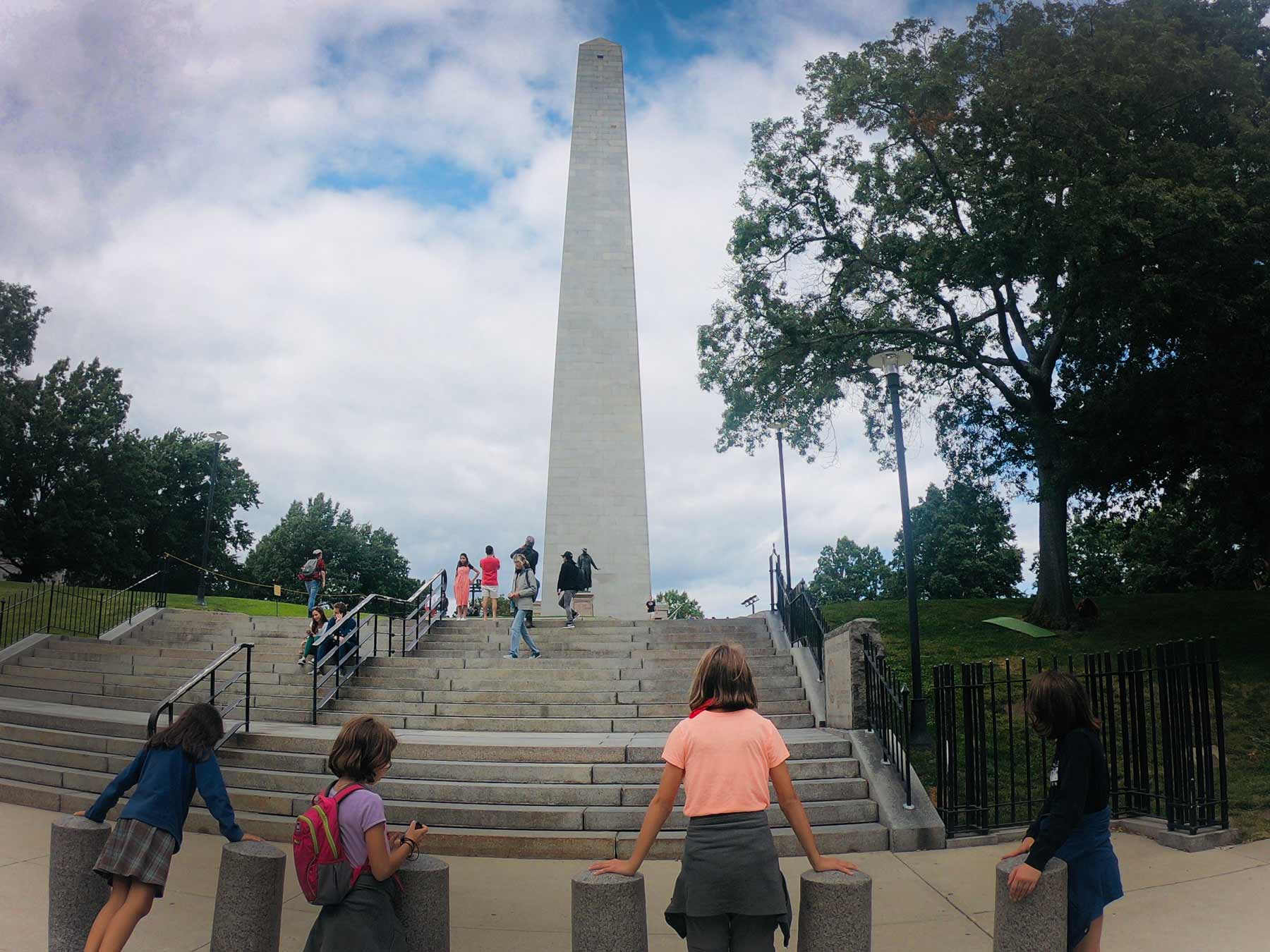 Teens looking at exterior of Bunker Hill Monument along the Freedom Trail in Boston, Massachusetts