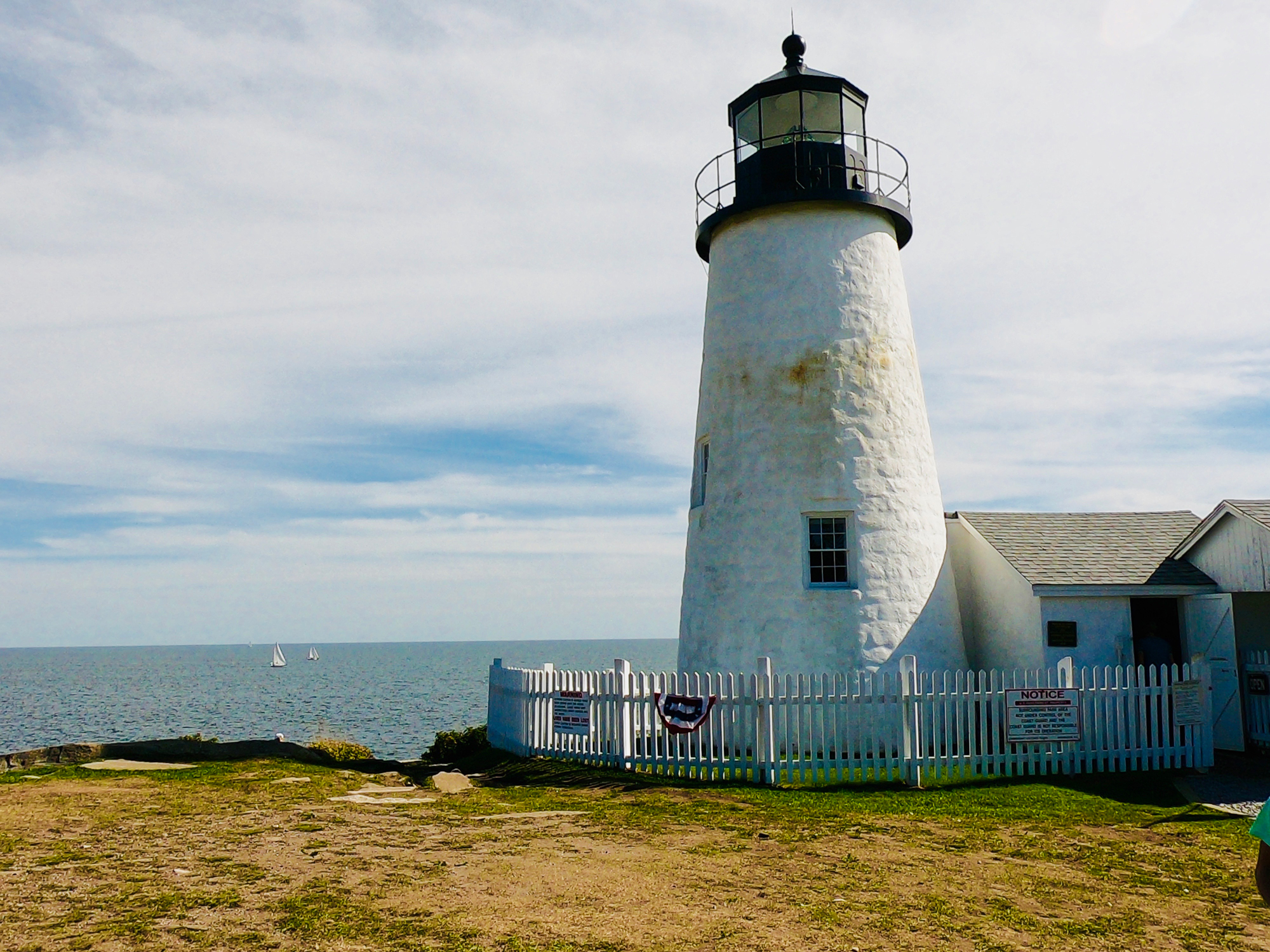 Exterior of Pemaquid Point Lighthouse with white picket fence overlooking bay with sailboats in Maine.