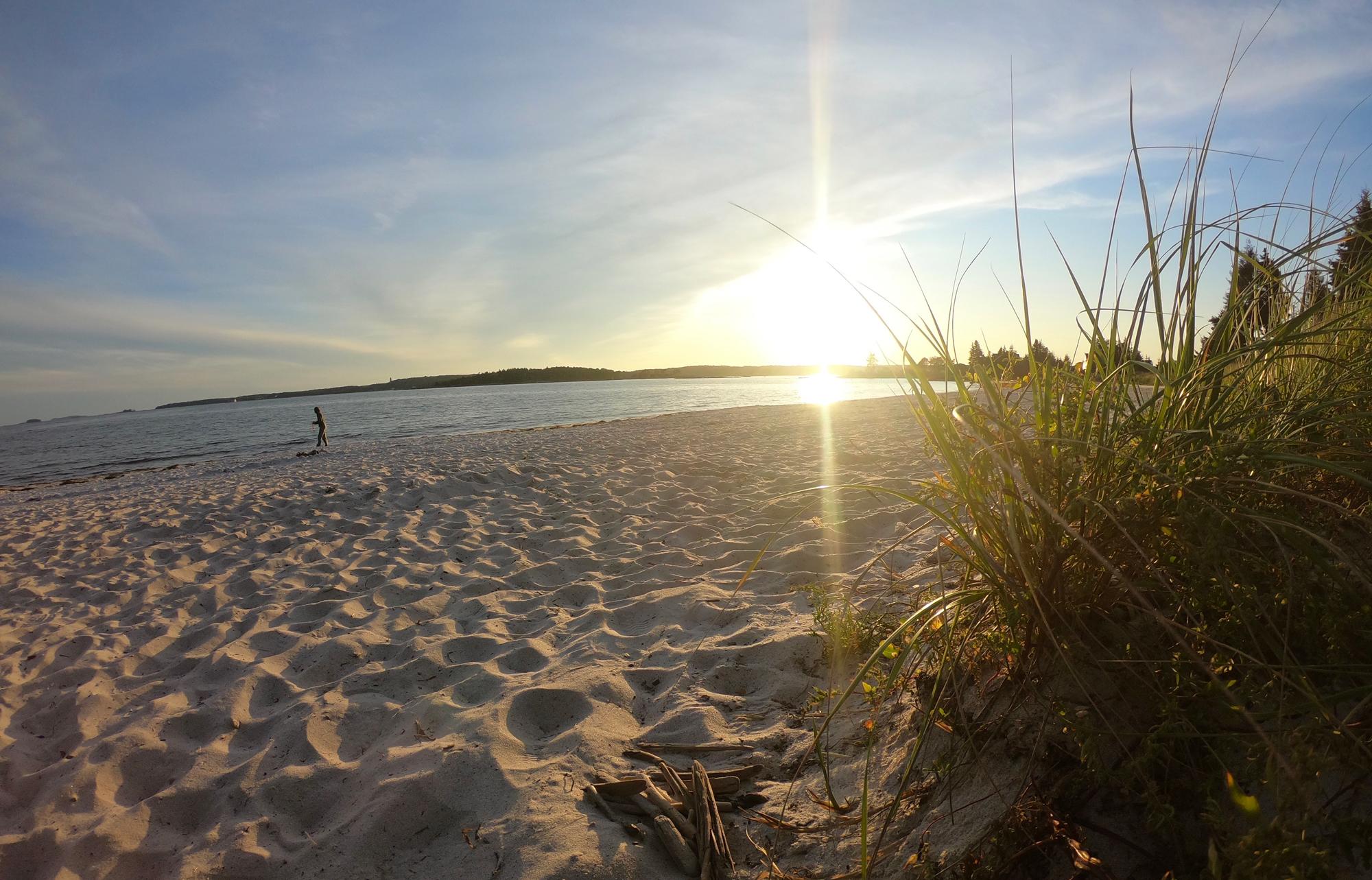 Child playing at sunset at Pemaquid Beach Park, Maine