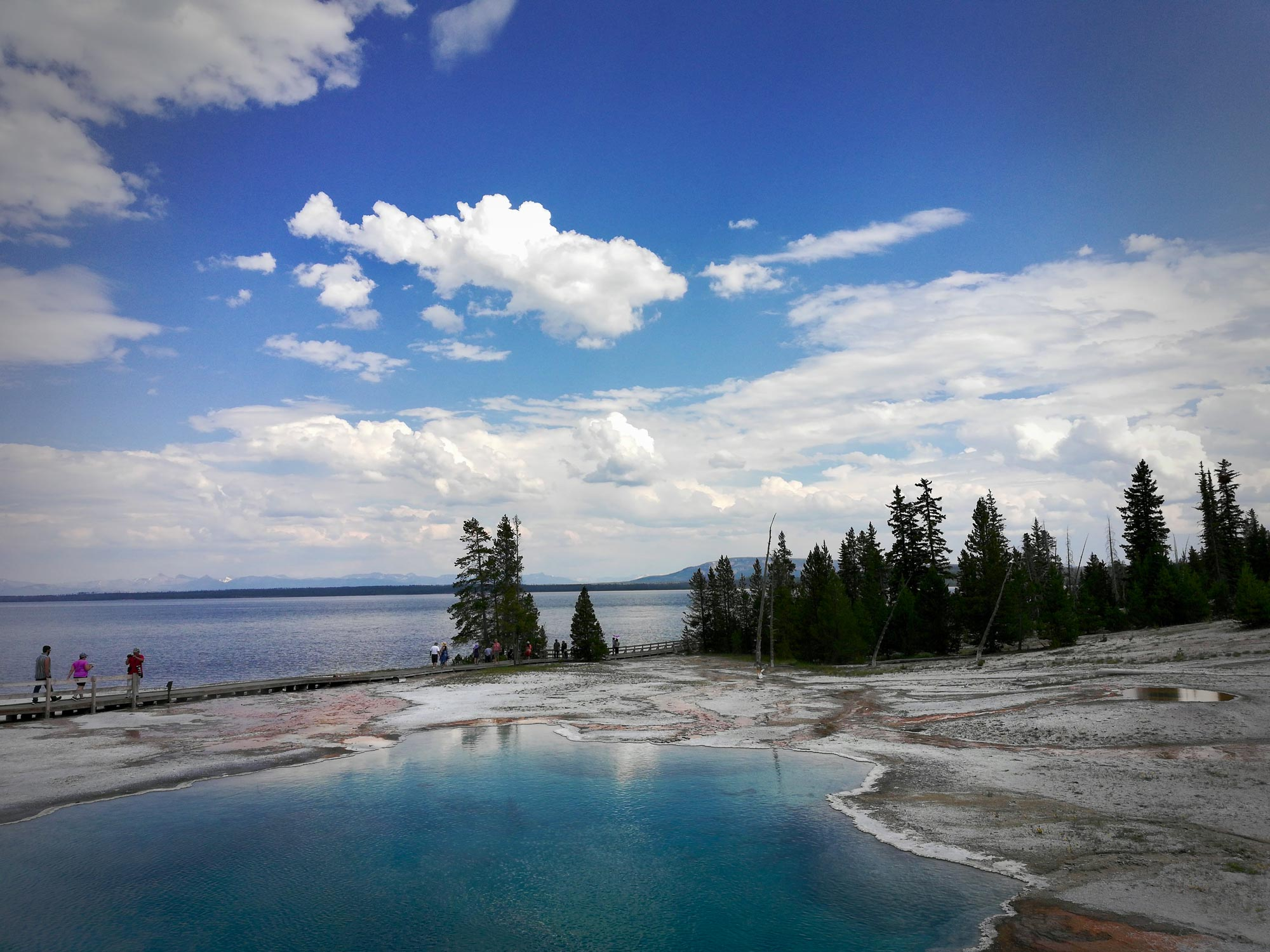 Abyss pool at west thumb geyser basin with Yellowstone Lake in Yellowstone National Park