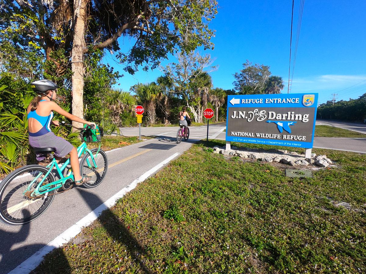 Two teen girls riding bikes in front of J.N.Ding Darling National Wildlife Refuge signage on Sanibel Island, Florida