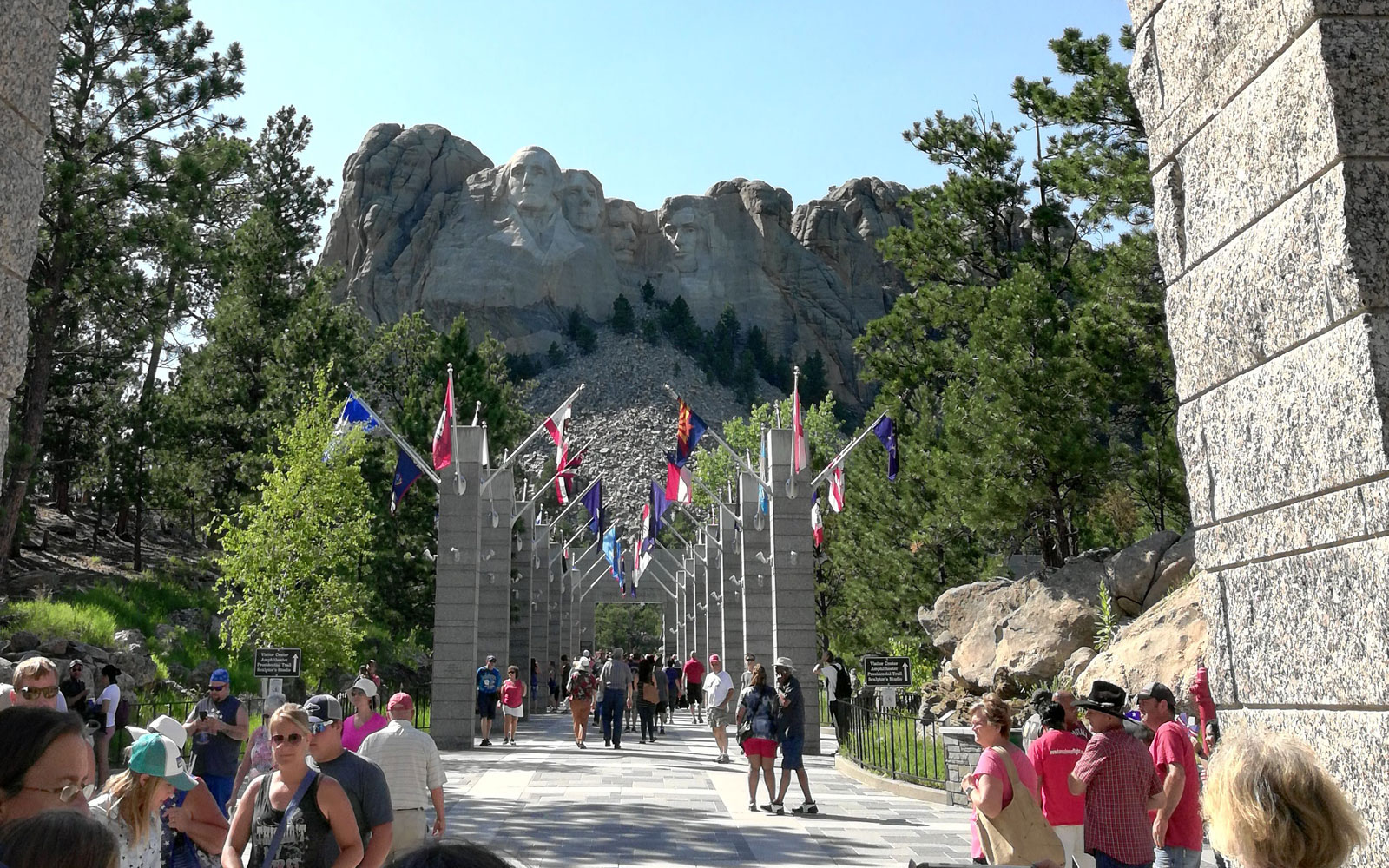 Avenue of Flags at Mount Rushmore, South Dakota on sunny day with crowds