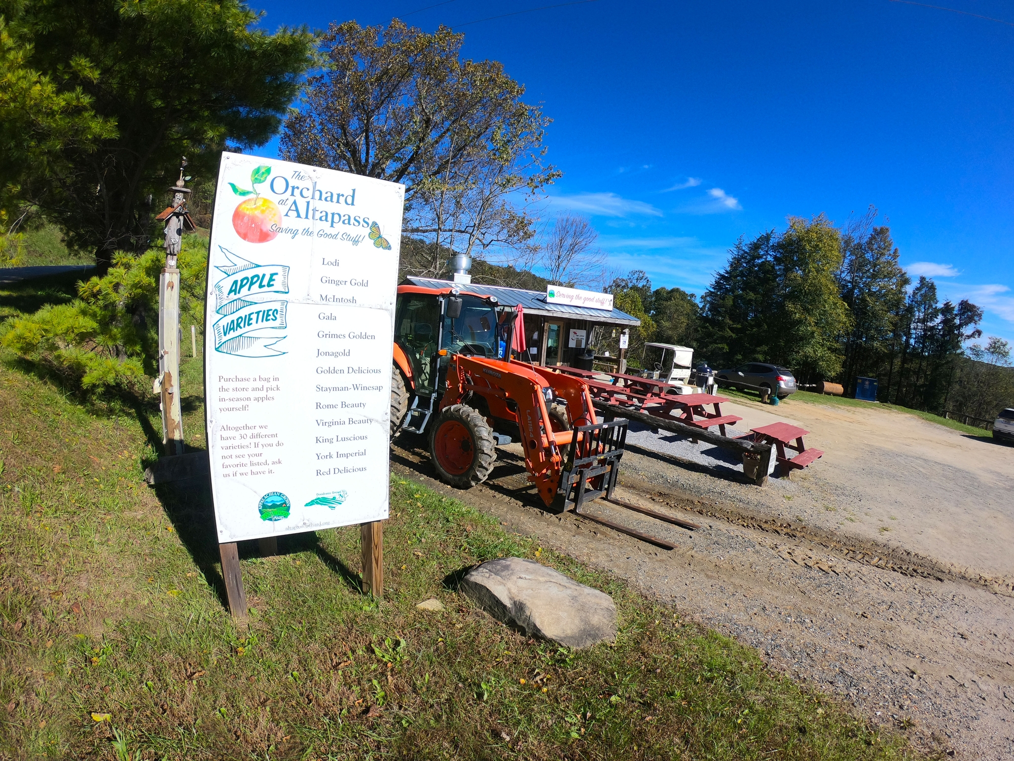 Image of gorgeous autumn day at The Historic Orchard of Altapass on the Blue Ridge Park in North Carolina with signage, tractors, and picnic tables