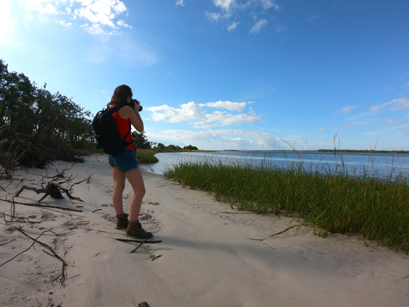 Photo of teenage girl wearing a backpack and photographing the Cape Fear River as she stands in the stand near the grassy edge of Carolina Beach State Park, North Carolina