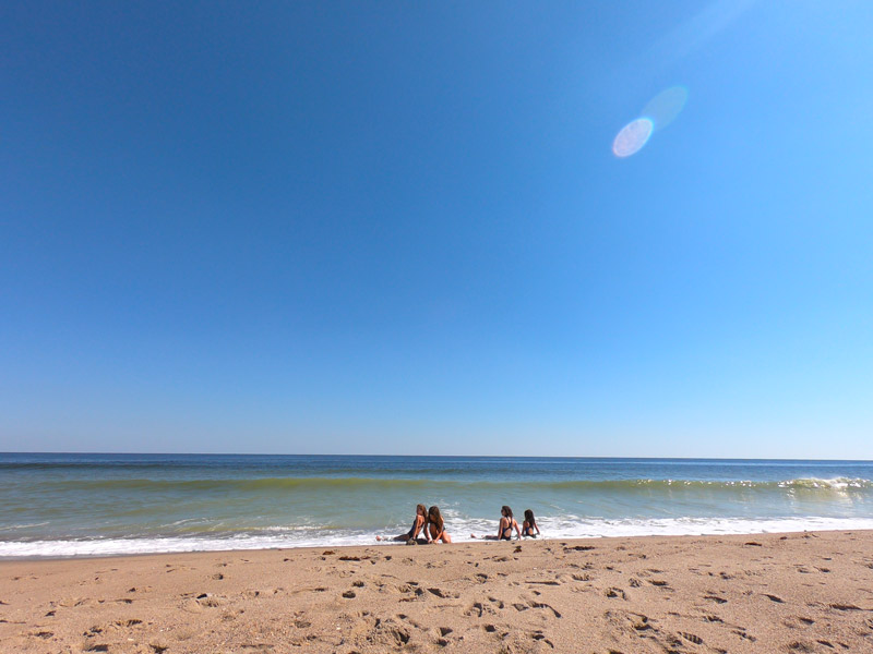 Photo of four sisters sitting in the surf on a gorgeous sunny day under a blue October Sky on Kure Beach, North Carolinal