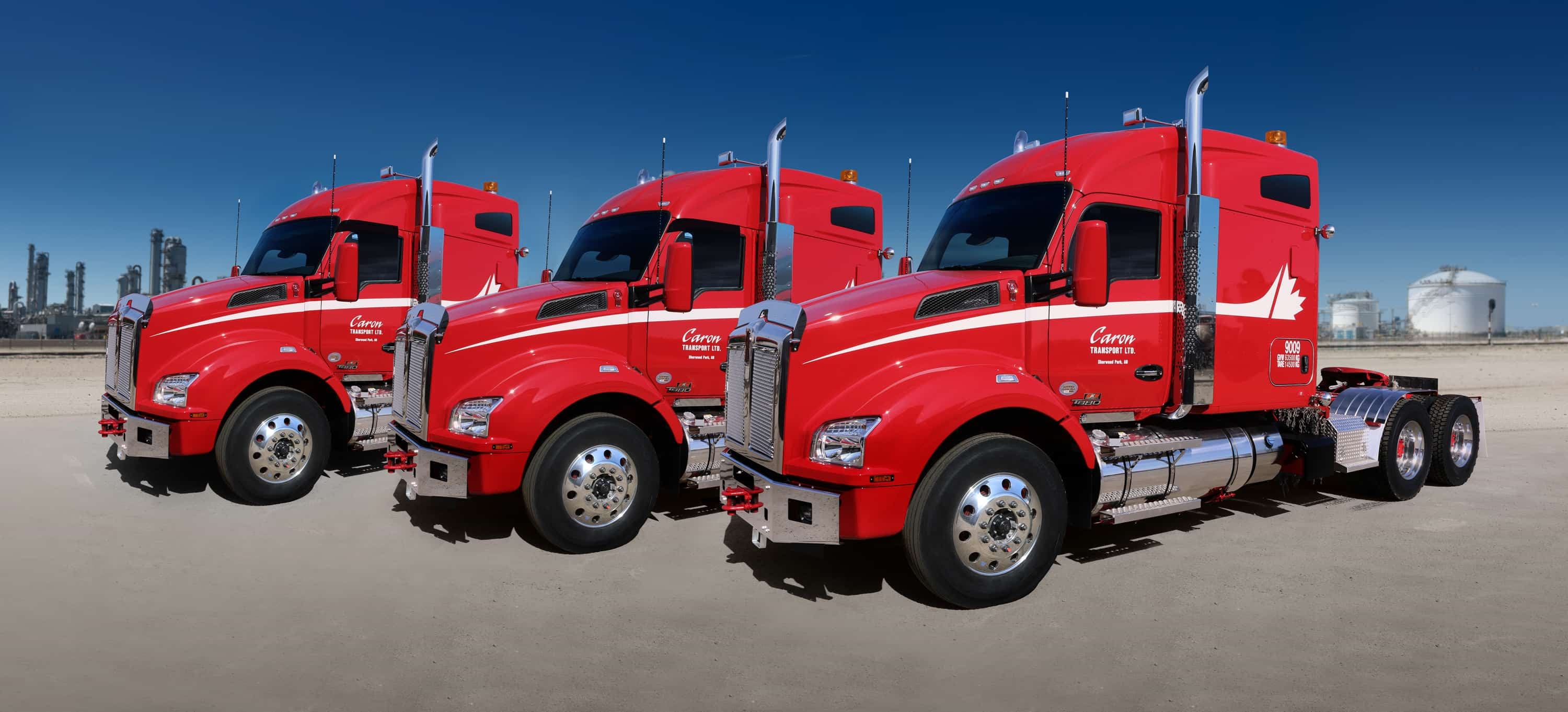 Three large semi-trucks branded with Caron logo and colours