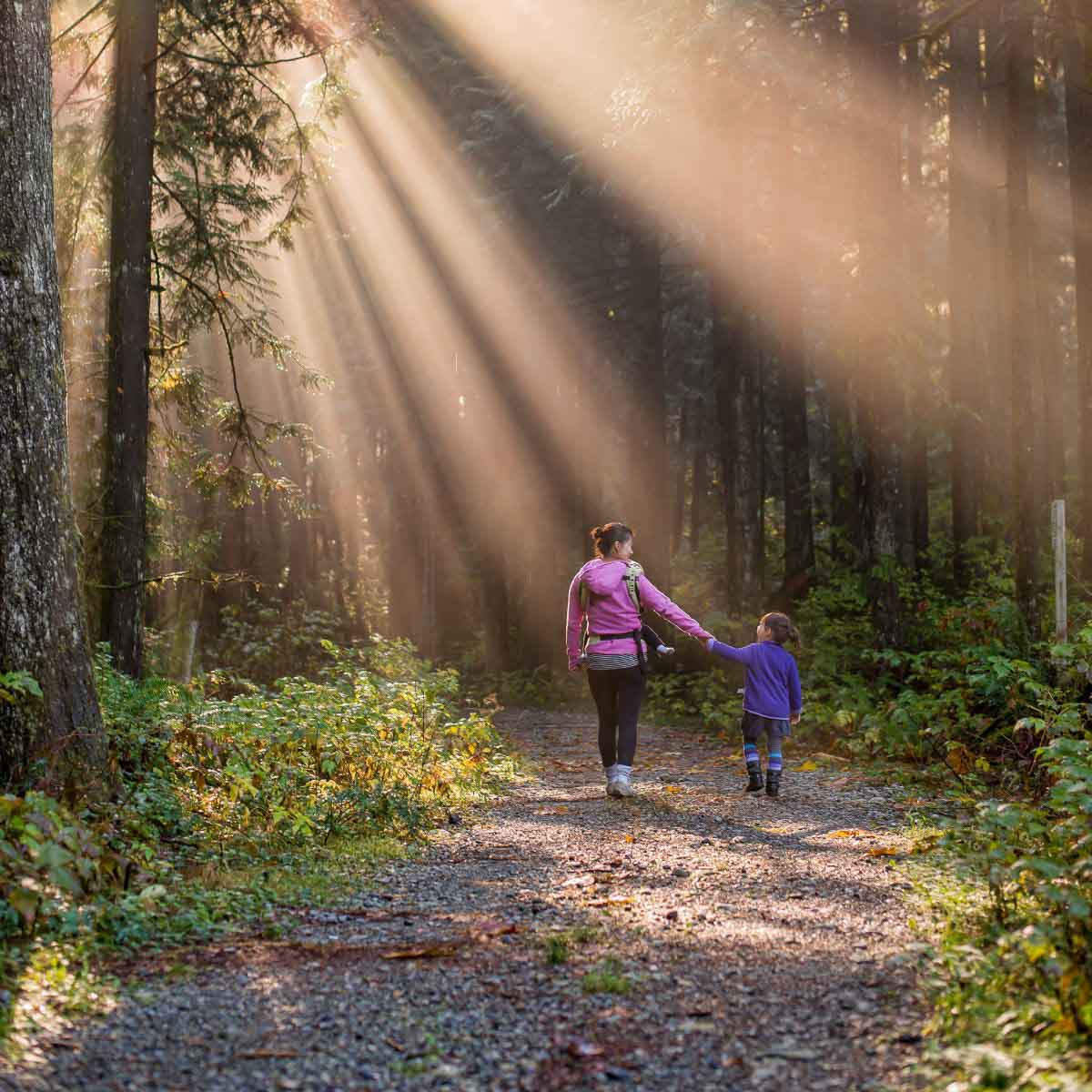 mom and daughter walking in the forest