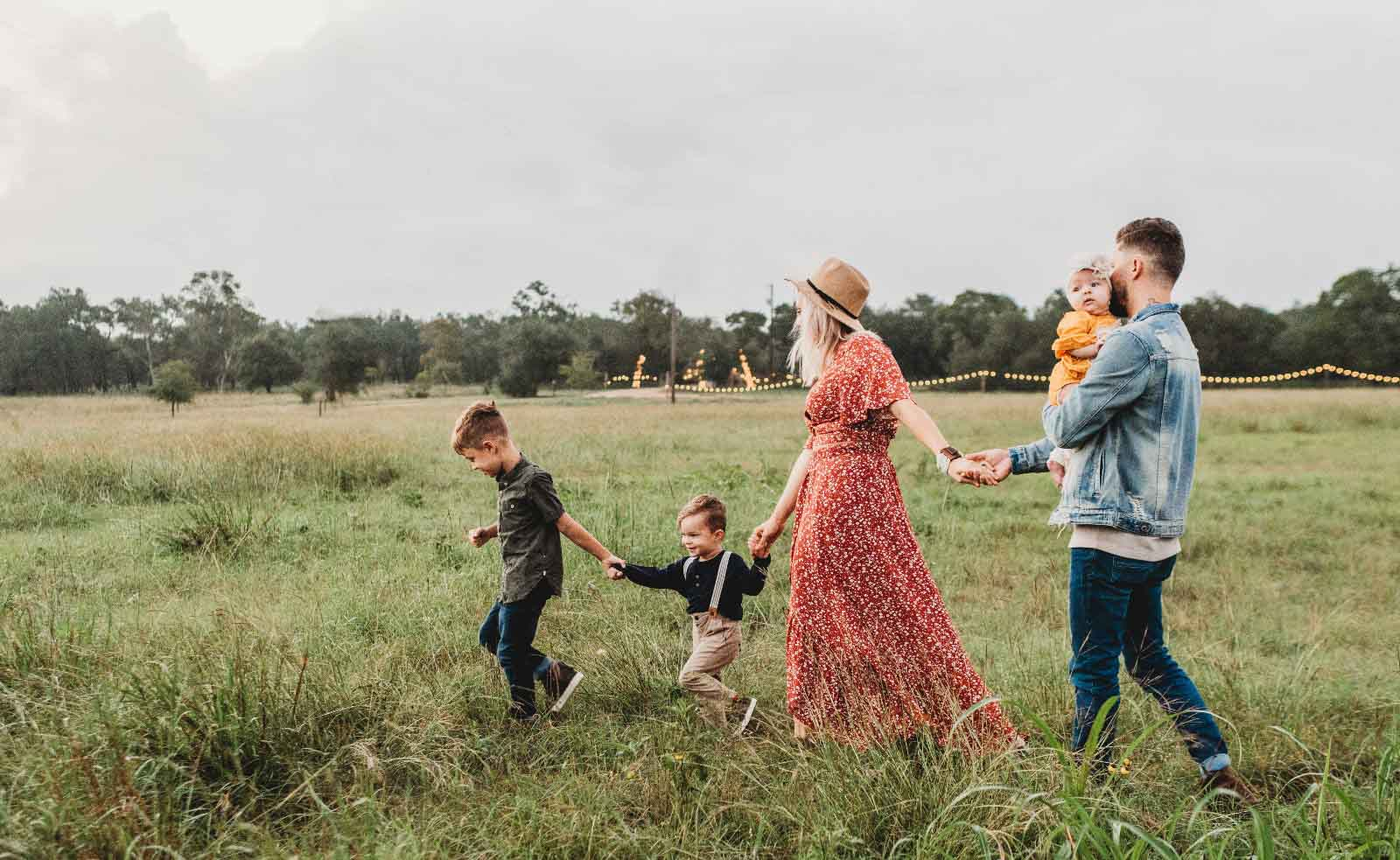 a family of four walking in a field