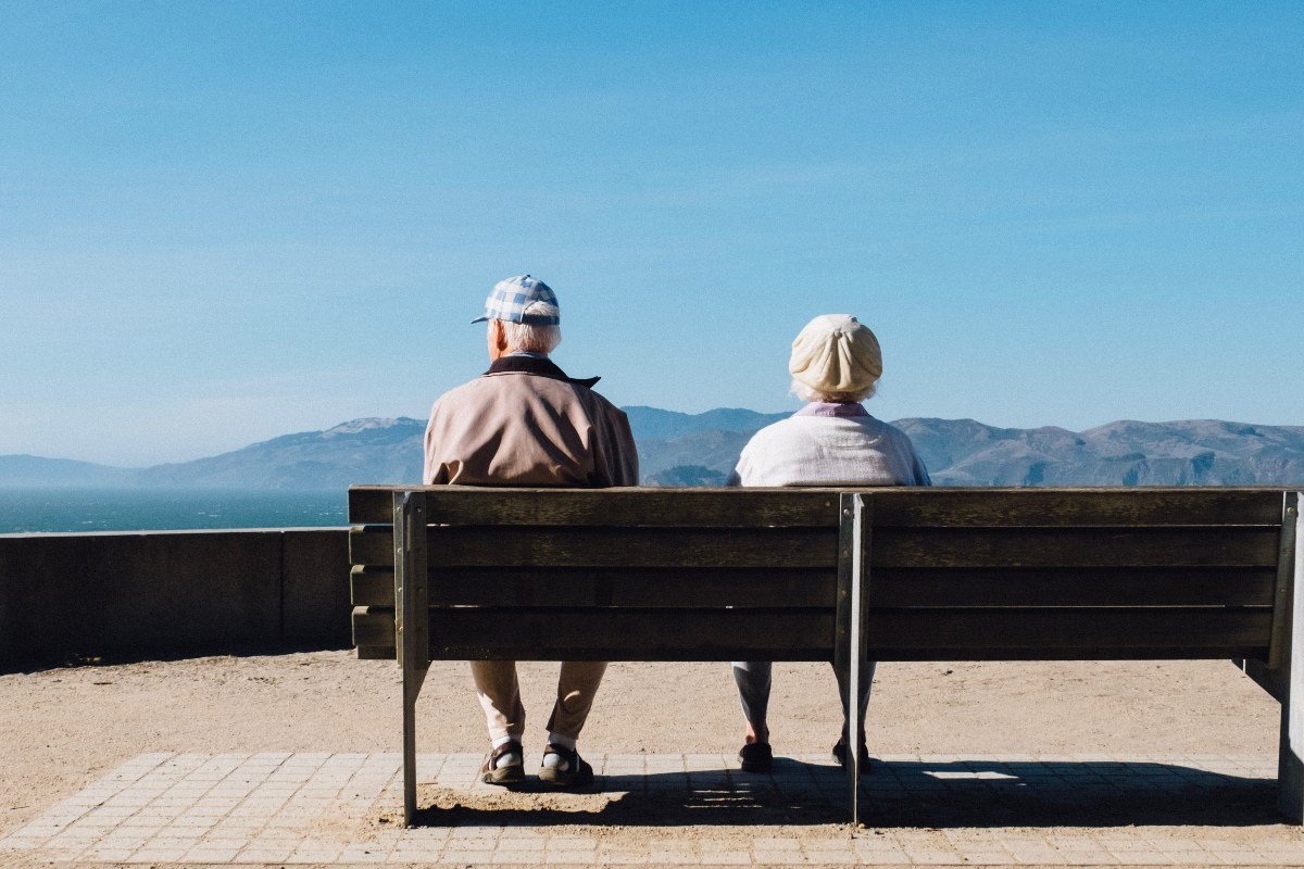 an elderly couple sitting on a bench looking out at a mountain