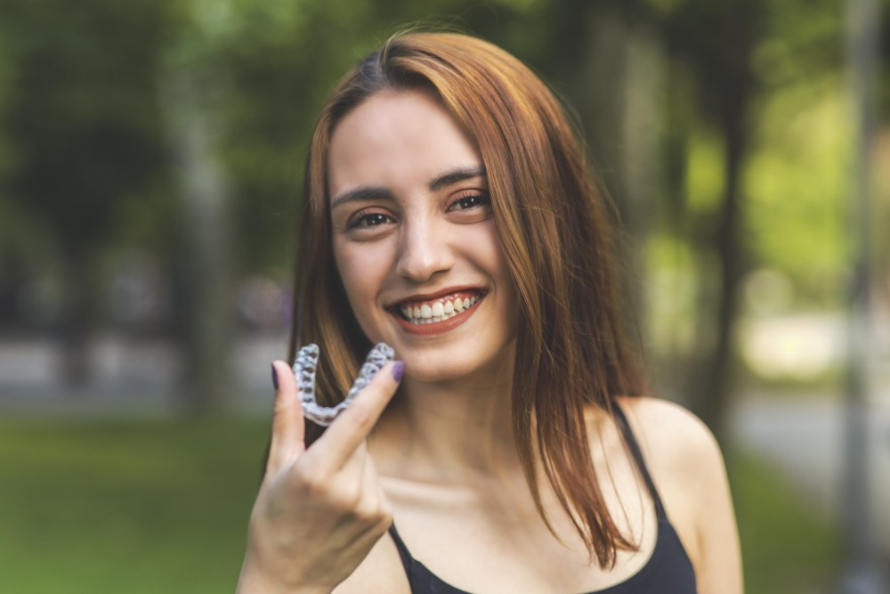 a teenage girl smiling and holding up invisalign