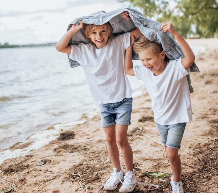 brothers walking along a lake smiling