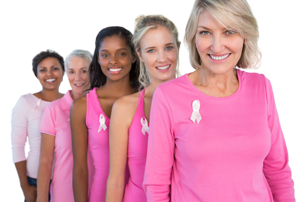 Cheerful women wearing pink and ribbons for breast cance on white background