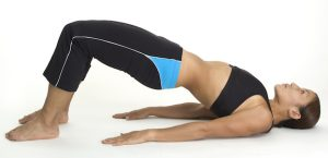 A female fitness instructor demonstrates the finishing position of the yoga bridge pose