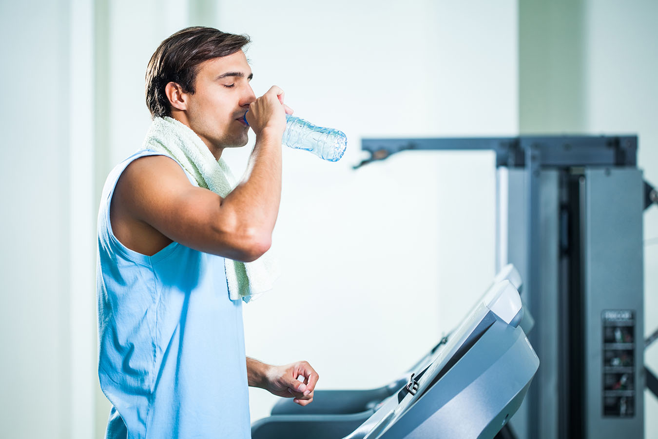 Man drinking water while exercising in gym