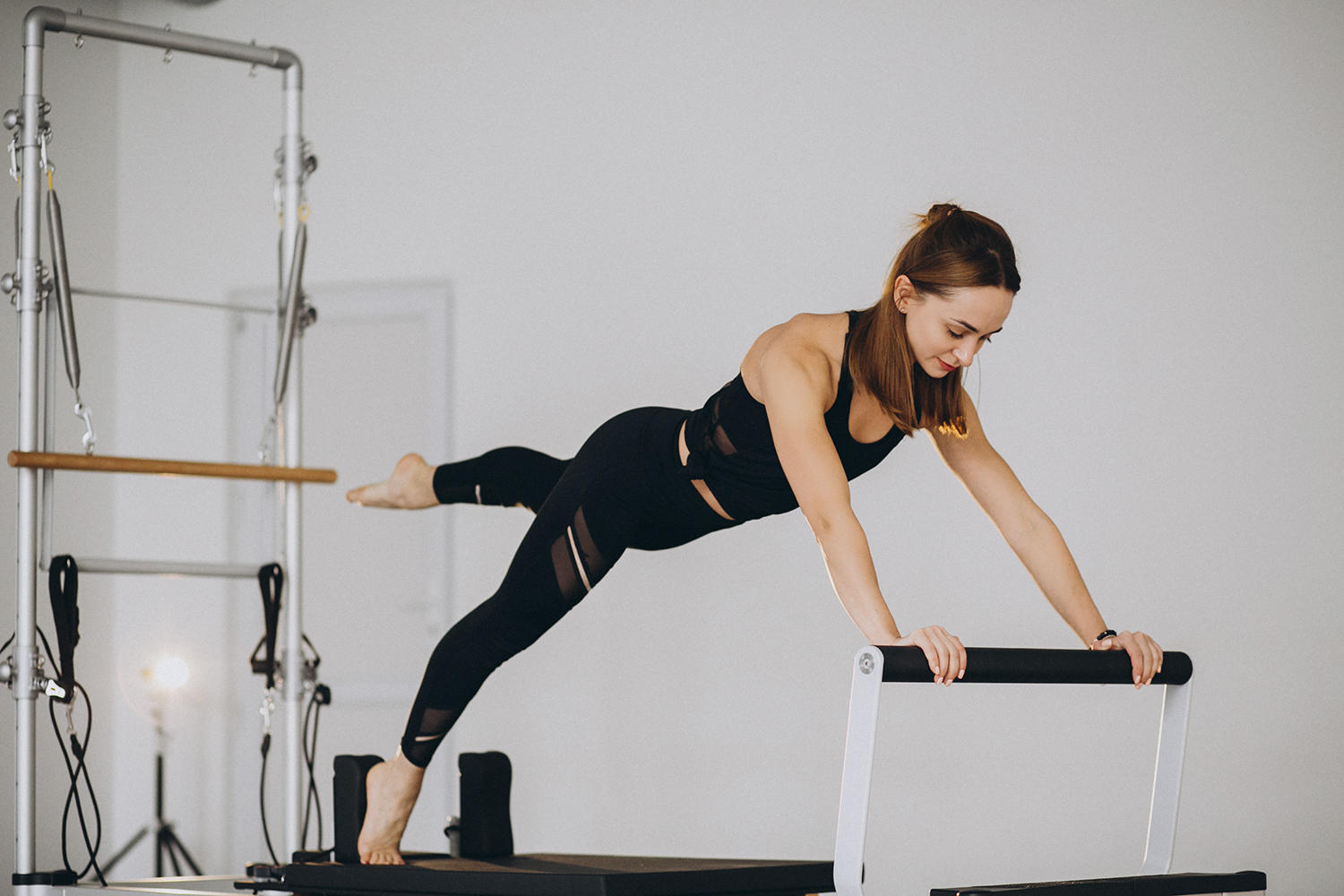 Woman doing pilates on a reformer|pilates|pilates-resources