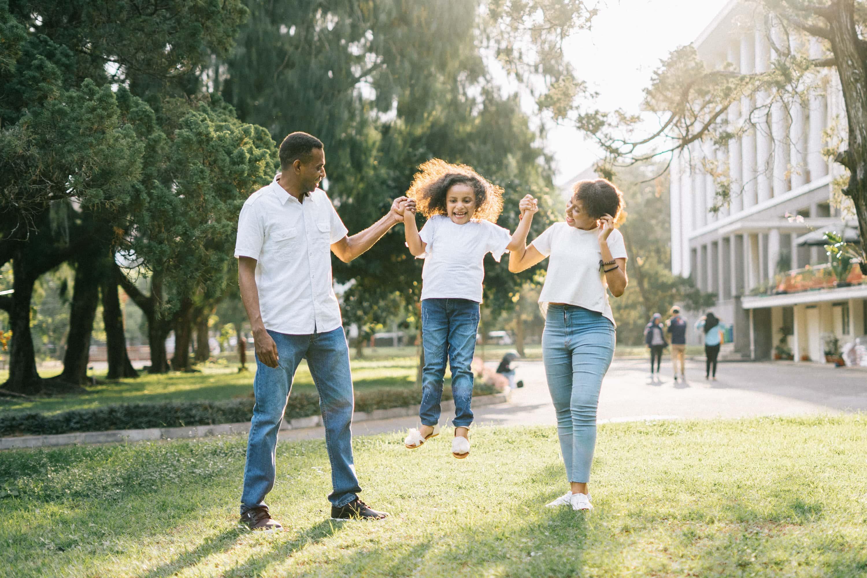 A family walks through a park holding hands.