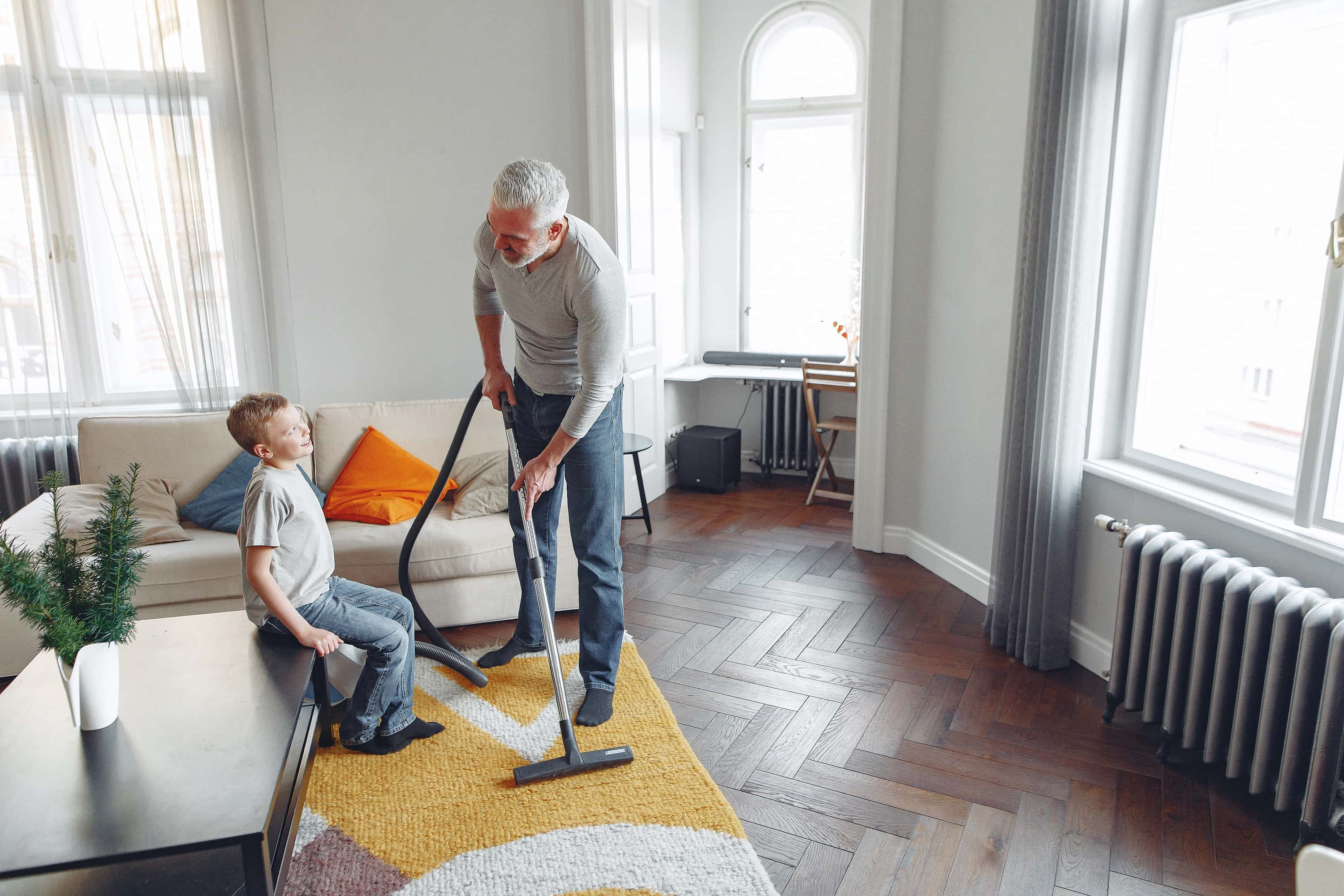 A man and his son vacuum together.