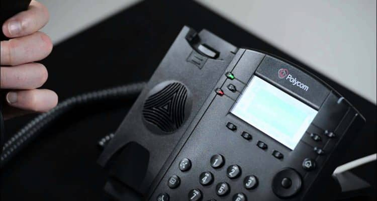 close up picture of someone holding the receiver of a desktop phone