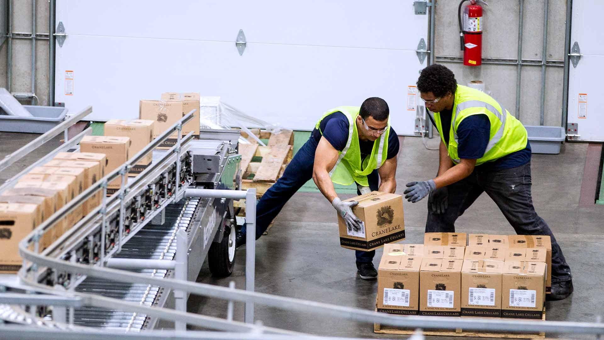 Two young men grab wine cases from a conveyer belt and place them on a pallet