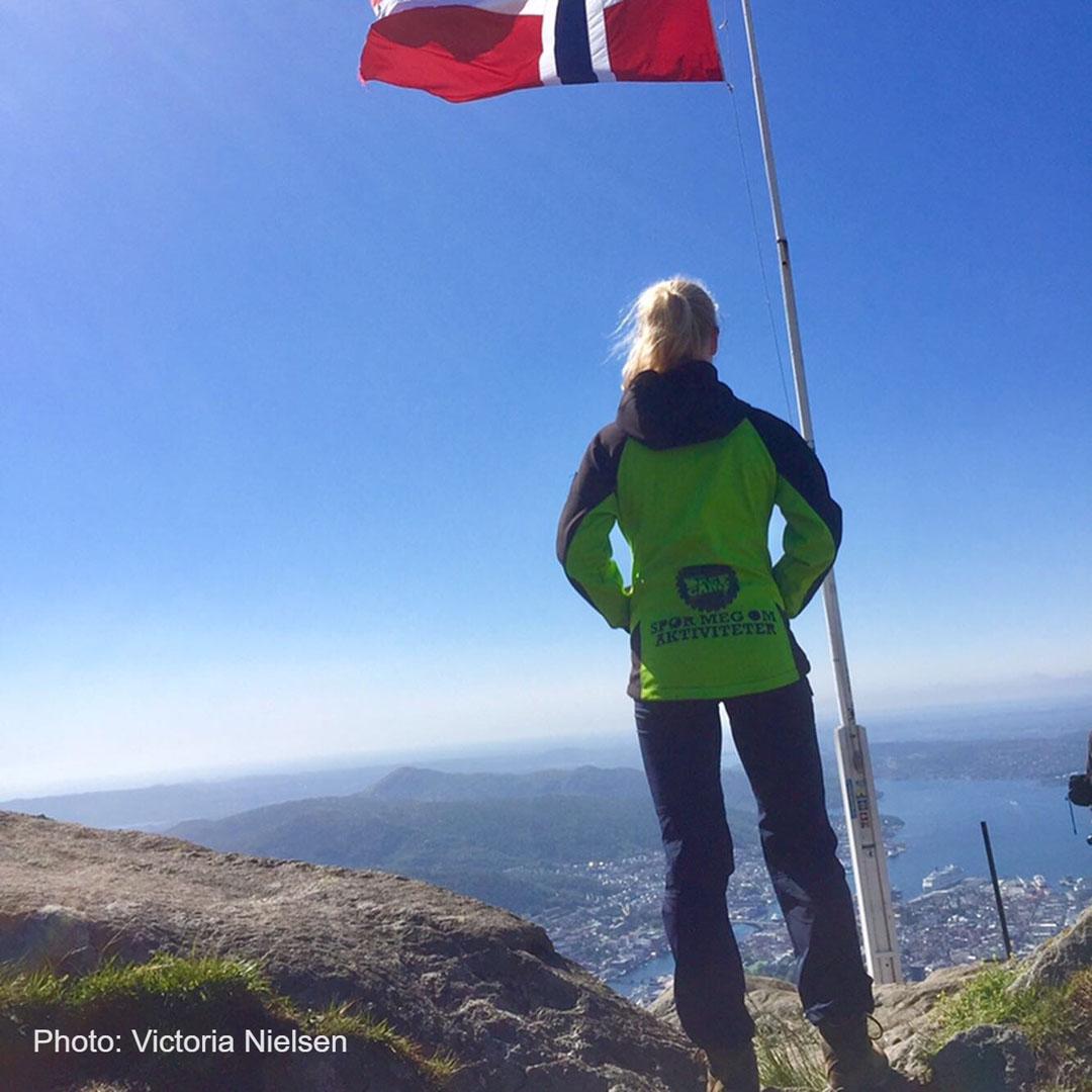 Bergen Base Camp guide på toppen av et fjell med et norsk flagg