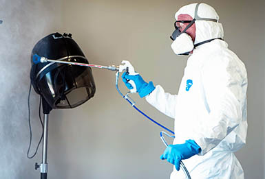 Image for Bill Glick Disinfecting showing Bill Glick in a white clean suit from the side disinfecting a hair dryer in the interior of a commercial retail business with a disinfecting sprayer.