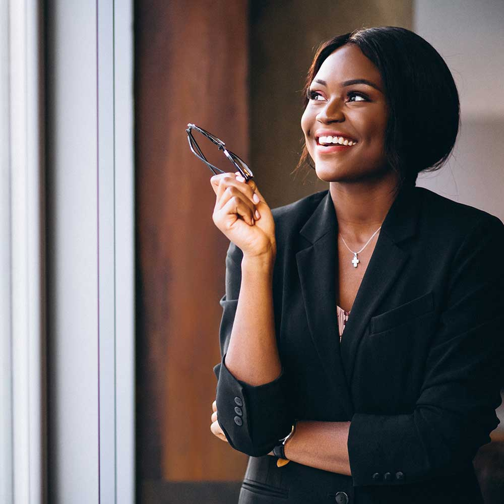 Woman looking out of window in office, smiling